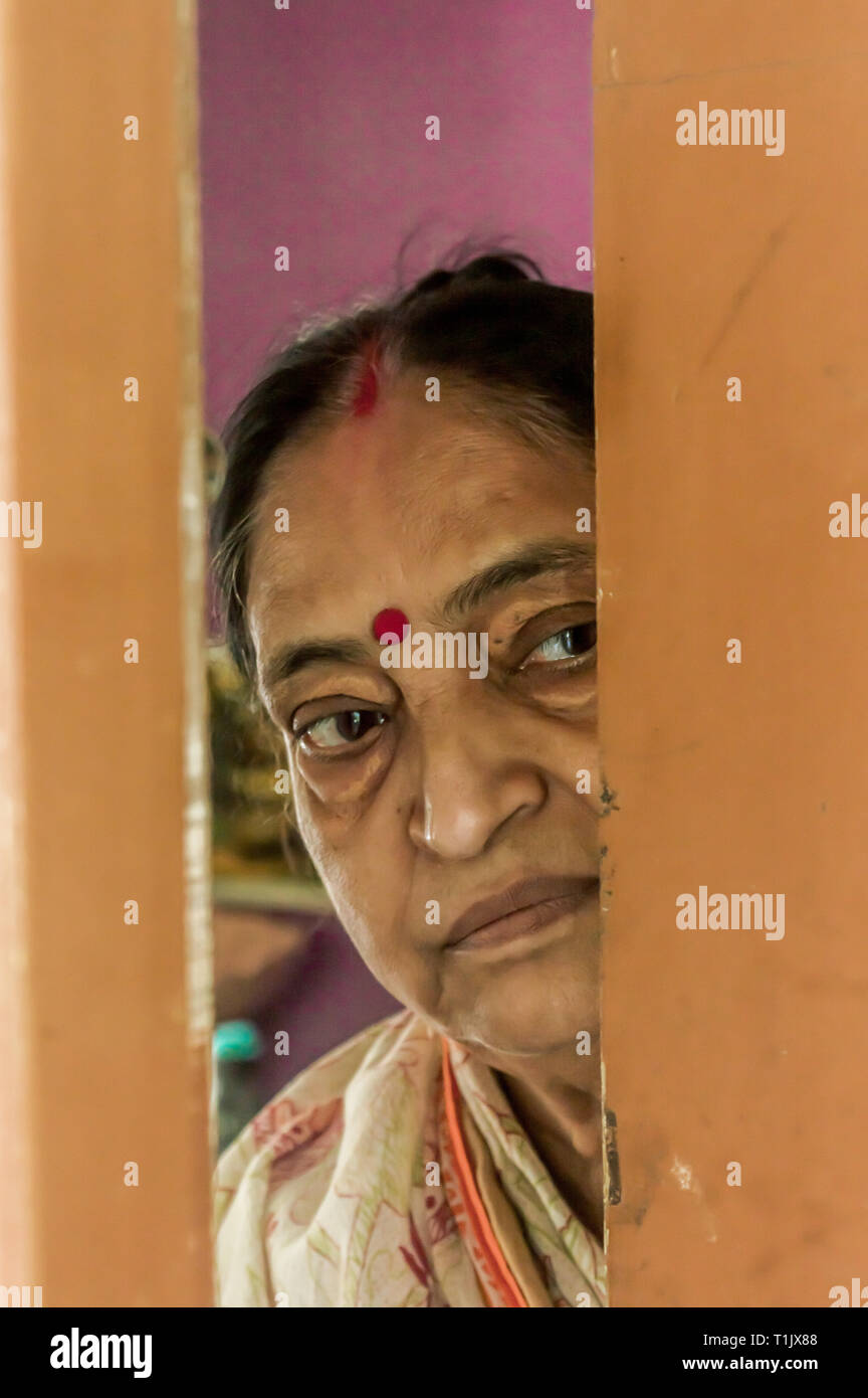Thoughtful, sad, Worried and alone elderly senior woman peeping through the door at home and eagerly waiting for her son to come. Loneliness concept - Stock Image