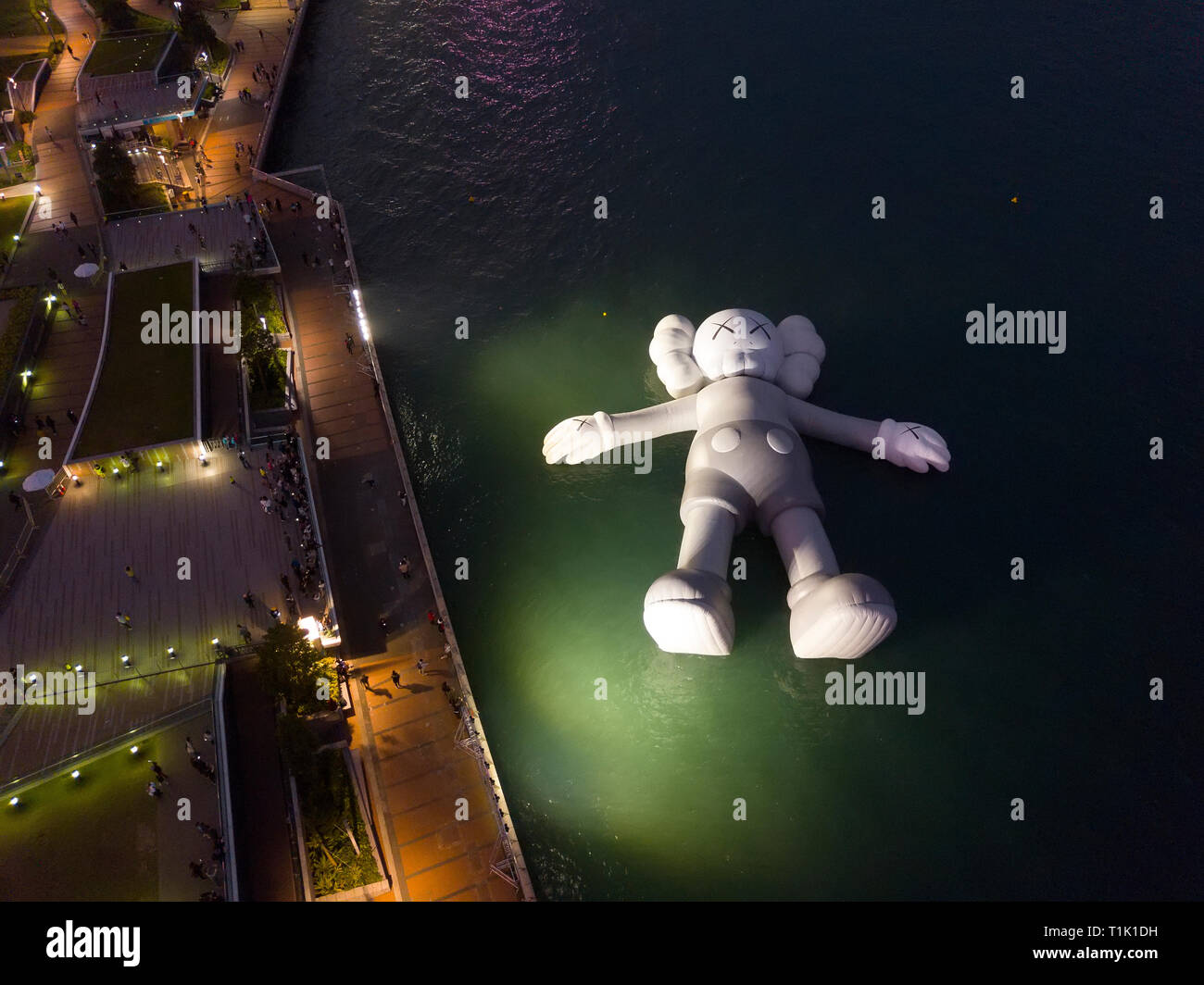 Hong Kong, China. 26th March, 2019. American artist and designer Brian Donnelly, Kaws Holiday Installation is currently on display floating in Hong Kong at the waterfront on Victoria Harbour. Hong Kong, China. Credit: Bob Henry/Alamy Live News Stock Photo