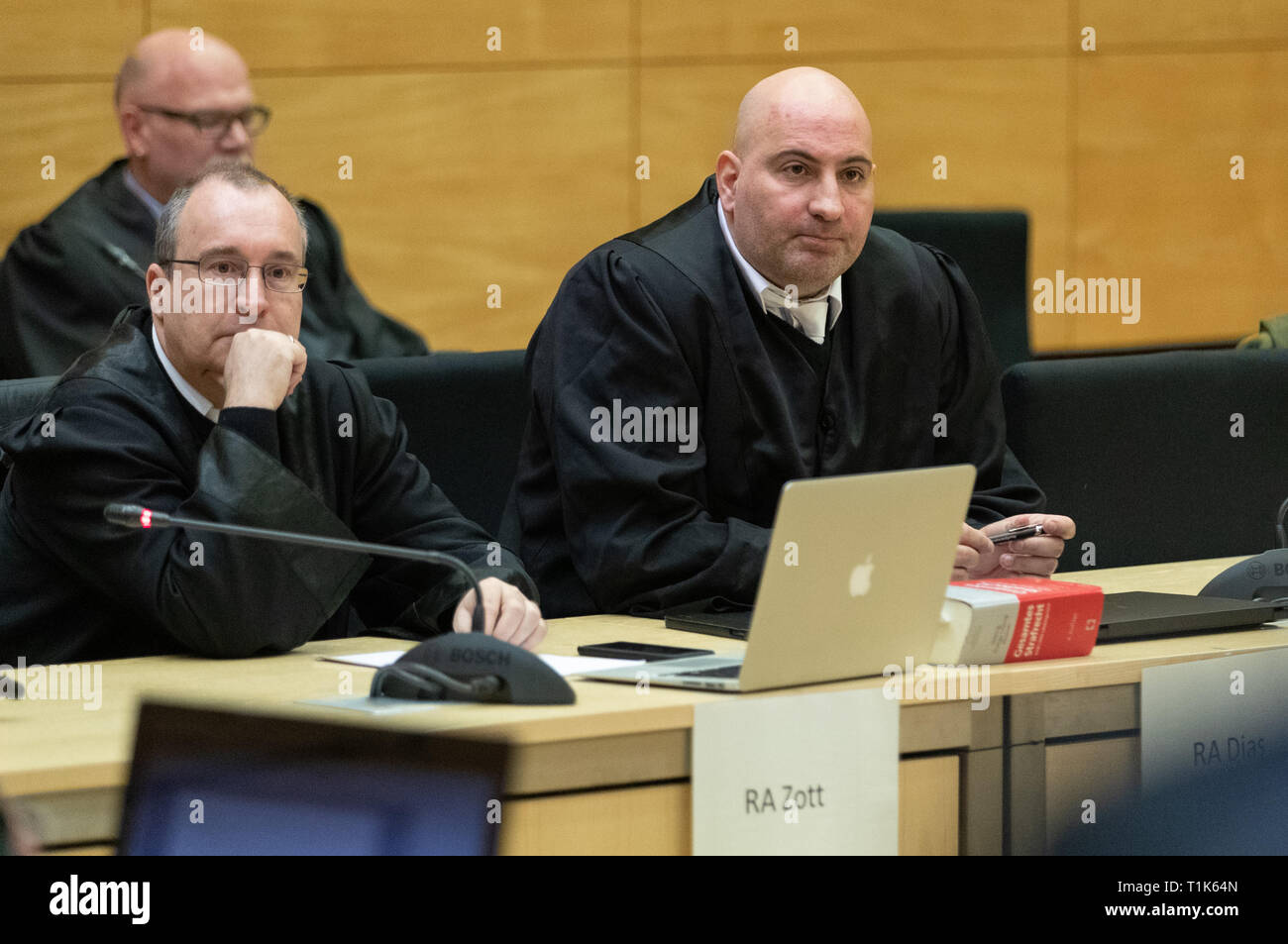 Bielefeld, Germany. 27th Mar, 2019. The defenders of the accused, Andreas Zott (l) and Paulo Dias (r), sit in a hall of the district court. A trial against eight men on suspicion of a serious breach of the peace begins under great security precautions. The defendants, aged between 20 and 38, are to belong to an extended family. After an argument, one of the men was expelled from a discotheque. The 27-year-old is said to have called his brother and other relatives to it. The argument escalated. Credit: Friso Gentsch/dpa/Alamy Live News Stock Photo