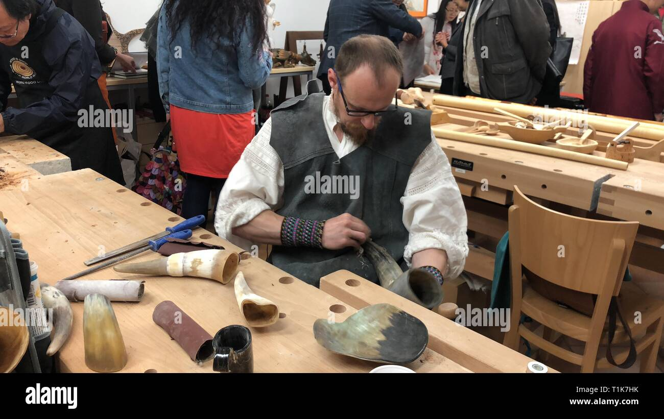 Bratislava, Slovakia. 27th Mar, 2019. An artist works during the World Wood Day workshop in Bratislava, Slovakia, March 27, 2019. The event not only invited a number of local European artists, but also a number of Chinese wood artists. Artists from Europe brought projects such as wooden musical instrument performance, wooden artworks processing and display, and wooden products making experience, while Chinese artists performed woodcut printing, woodcarving and calligraphy for audience. Credit: Jiang Xue/Xinhua/Alamy Live News - Stock Image