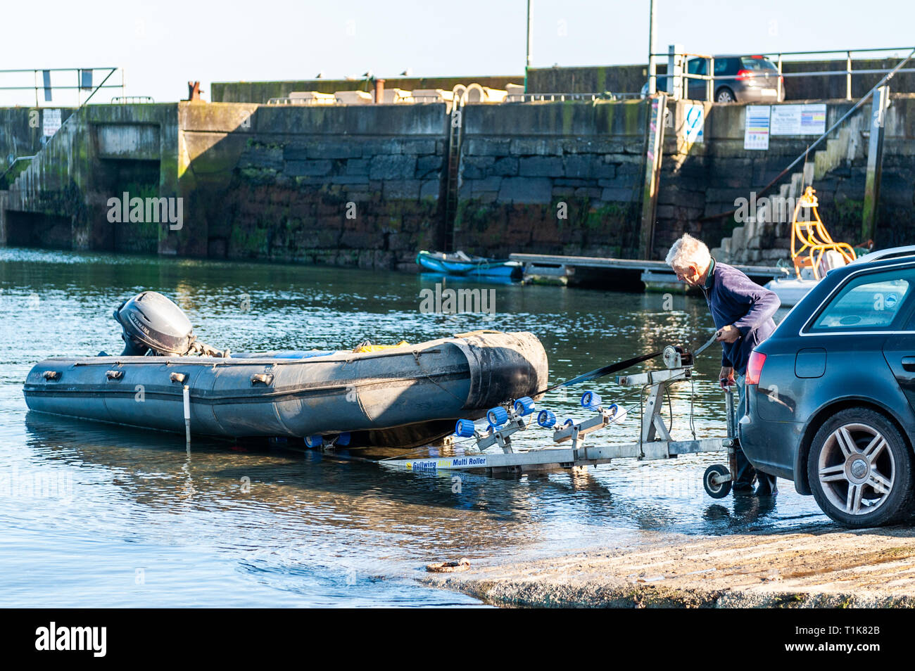 Schull, West Cork, Ireland. 27th March, 2019. A man launches his RIB off Schull Harbour slipway at the end of a beautiful day in West Cork. The remainder of the day will be sunny with highs of 12° Celsius. Credit: Andy Gibson/Alamy Live News. - Stock Image