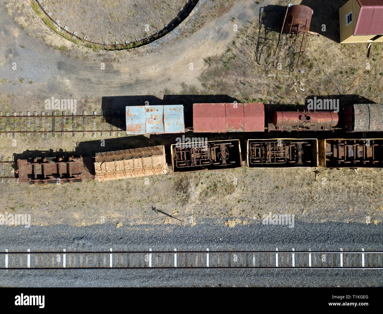 Old train tracks, train turntable, train yard cars and train yard above aerial view next to modern day train line. Victoria, Australia. - Stock Image