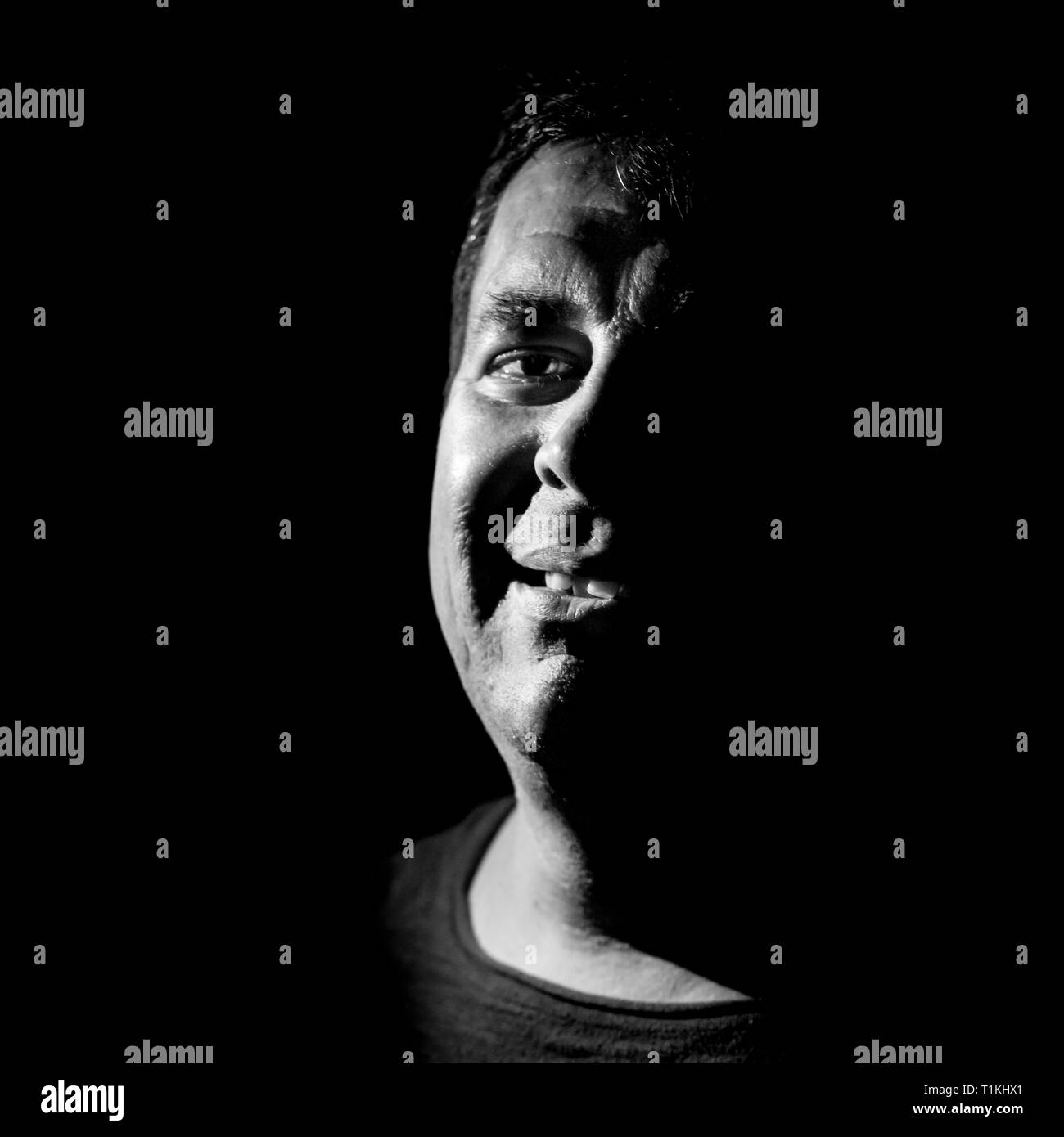 Stylish portrait of adult caucasian man. He smiles like maniac and seems like maniac or crazy. Black and white shot, low-key lighting. Angry man, fear - Stock Image