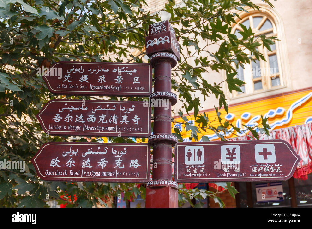 Multi-lingual directional signs in Kashgar Old Town. Pointing towards scenic spots (like Id Kah Mosque) and other useful destinations (like toilets). - Stock Image
