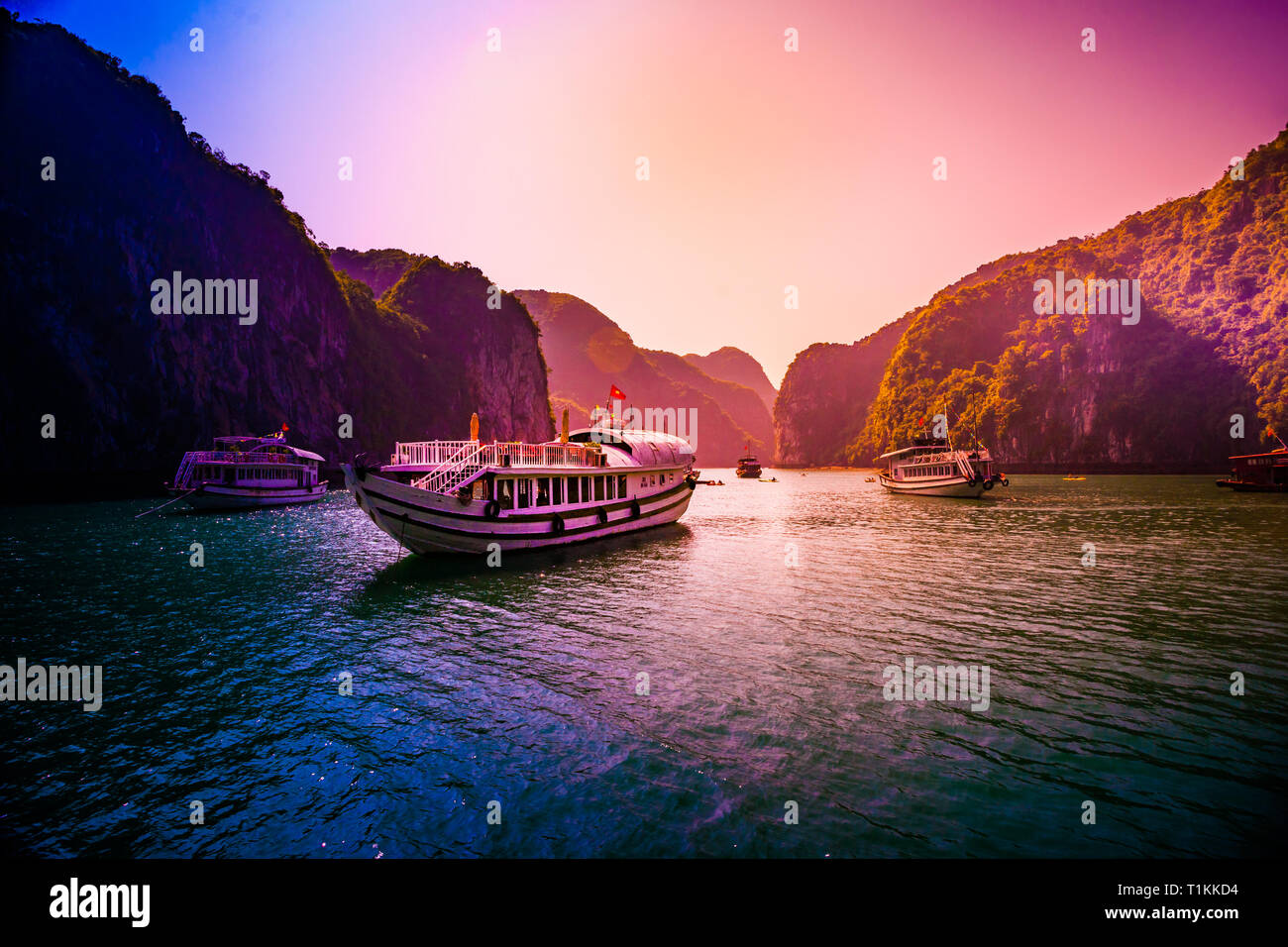 Sunset at Halong Bay Vietnam with tour boats in the foreground - Stock Image