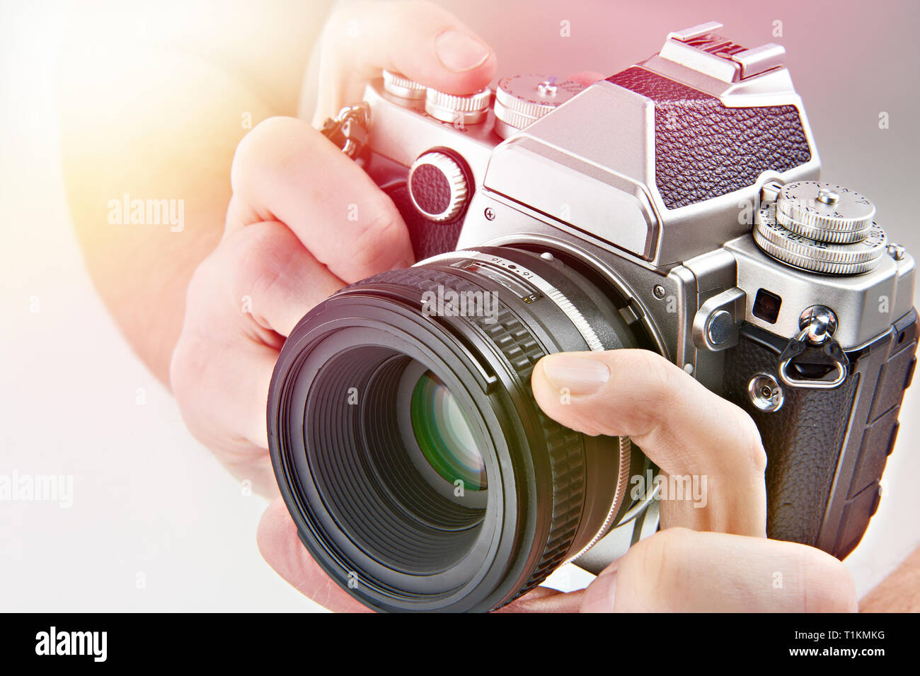 Retro SLR camera in the hands of the photographer closeup - Stock Image