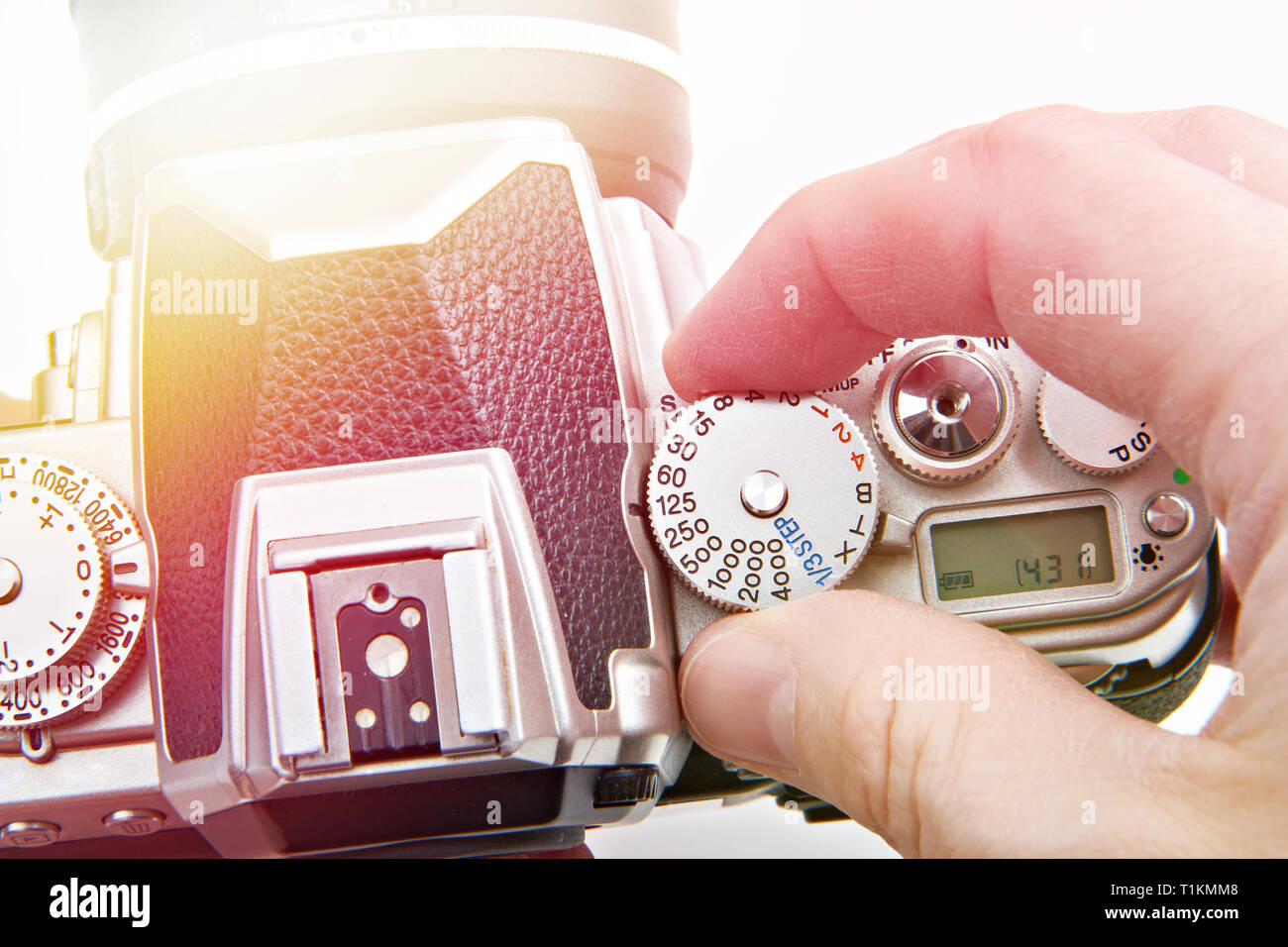 Photographer setting shutter control dial on retro SLR camera closeup - Stock Image