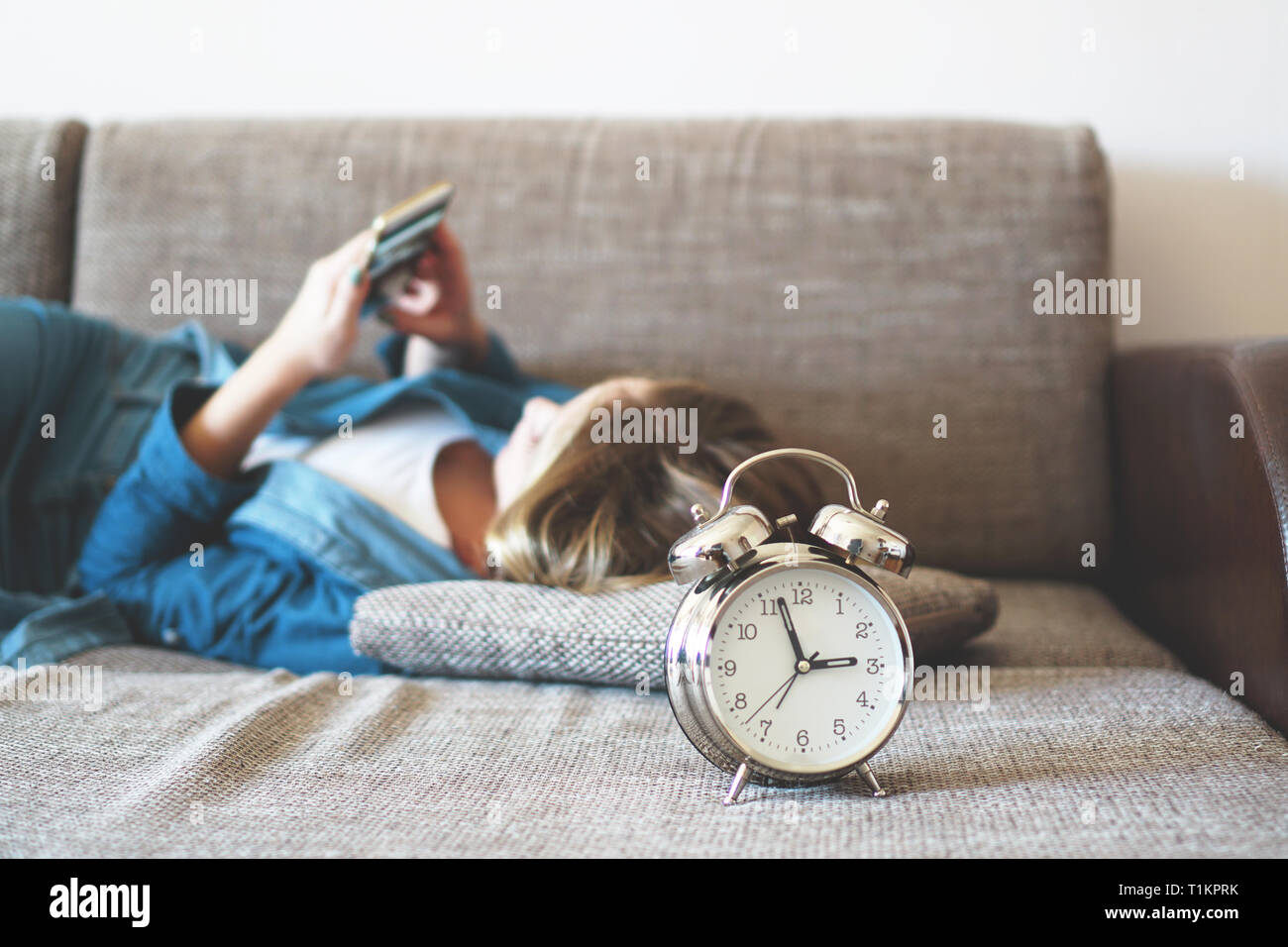 Young woman using phone in bed, looking at screen, insomnia, check time, wake up with smartphone, mobile phone addiction - alarm clock near - Stock Image