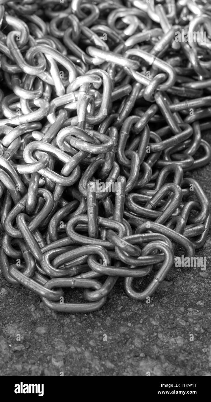 galvanized chain lies on the road under the rays of the Sun closeup - Stock Image