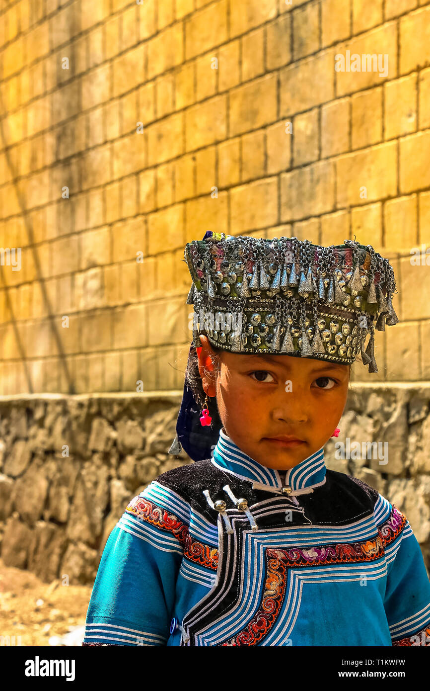 Yuanyang County, Yunnan, China - 2014: A Hani minority village girl wearing traditional headgear adornments - Stock Image