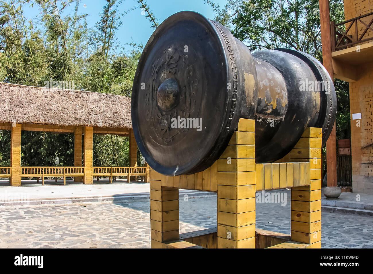 Yuanyang County, Yunnan, China - 2014: A bronze gilded drum at Qingkou Folk Village - Stock Image