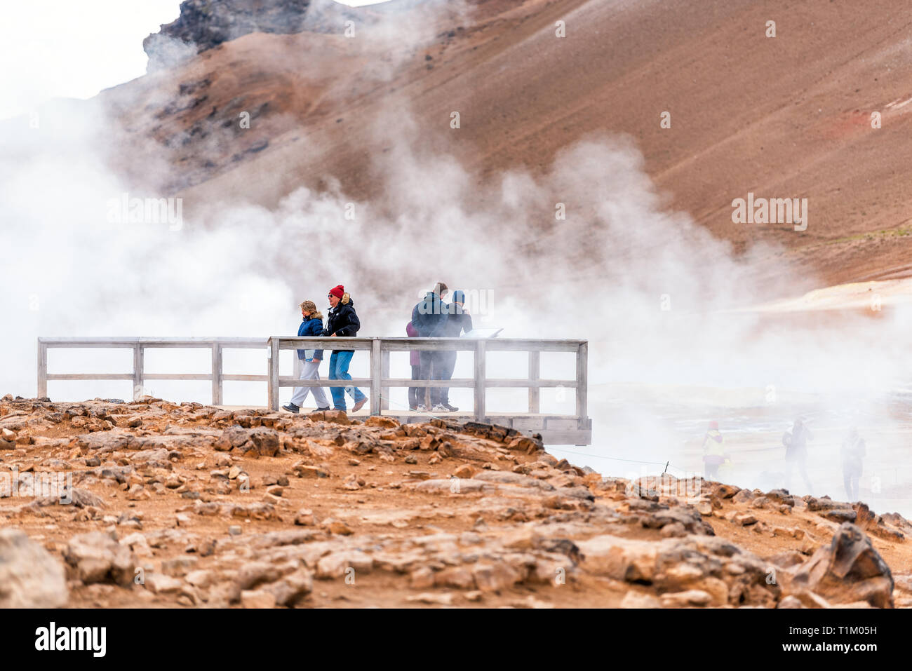 Hverir, Iceland - June 16, 2018: Hot steam vapor with people tourists looking at springs on wooden platform overlook covered in mist fog geyser in geo - Stock Image