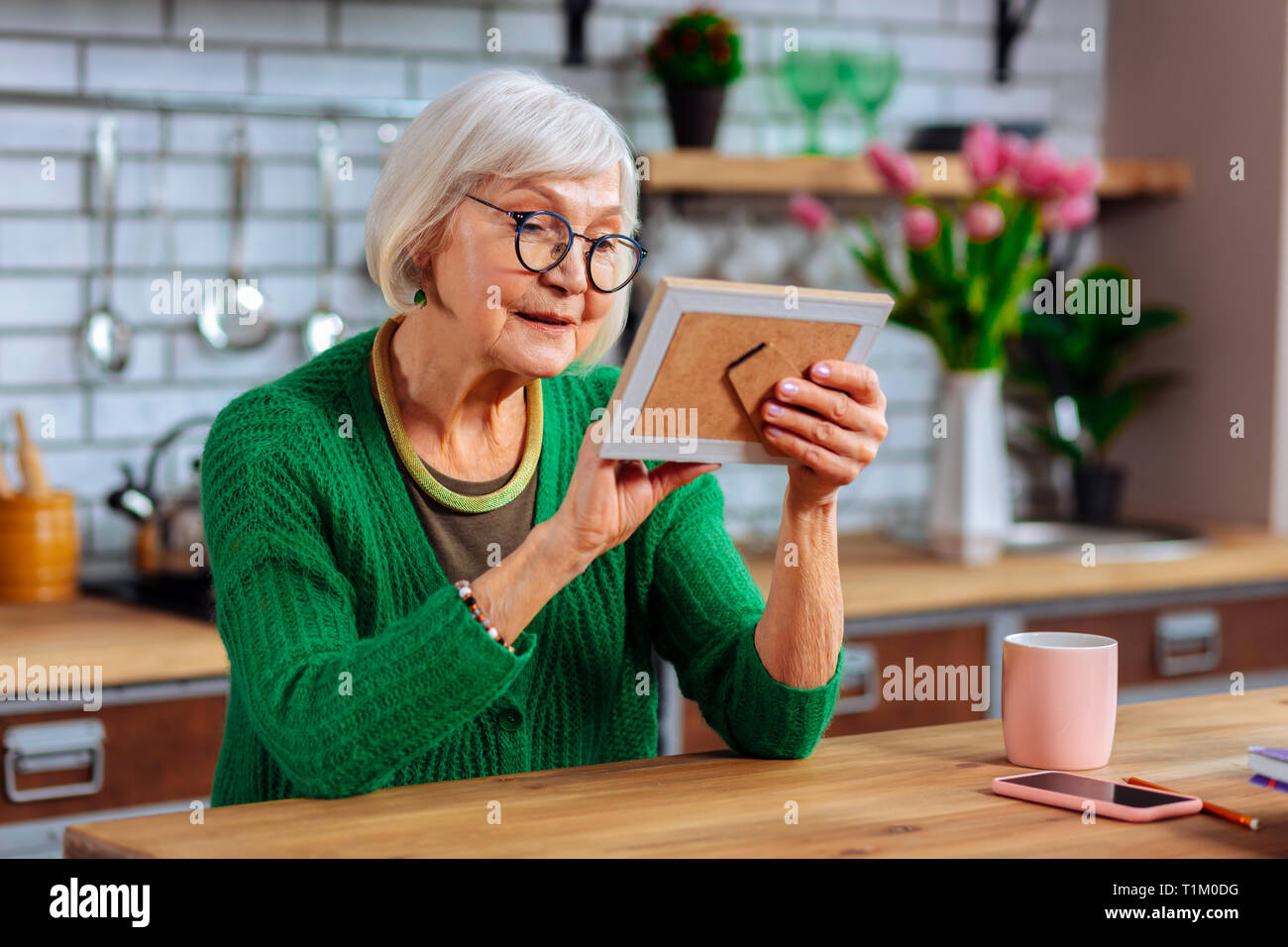 Aged woman tenderly palming photo frame while sitting at table - Stock Image