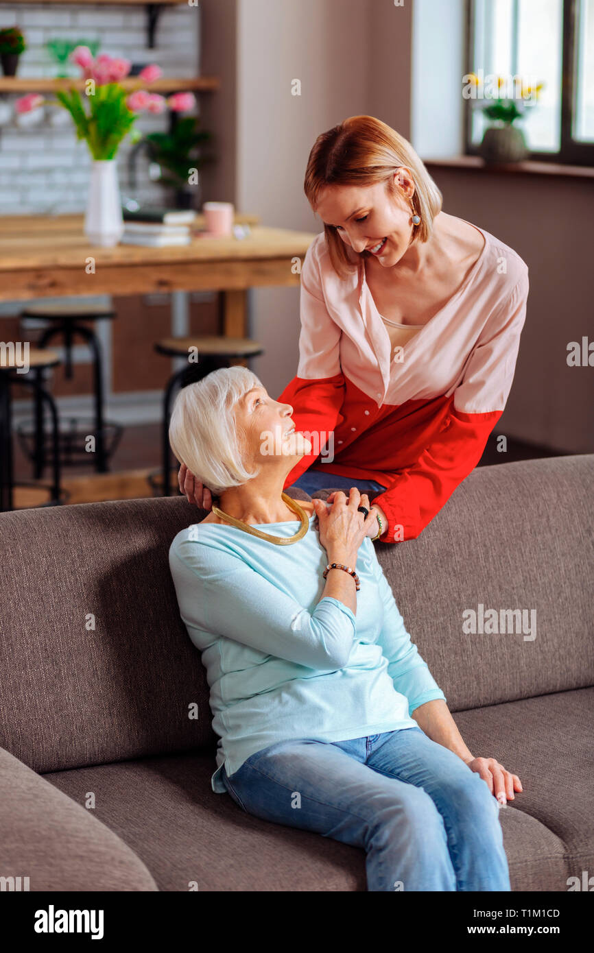 Happy adult lady tenderly palming mother hand and holding head - Stock Image