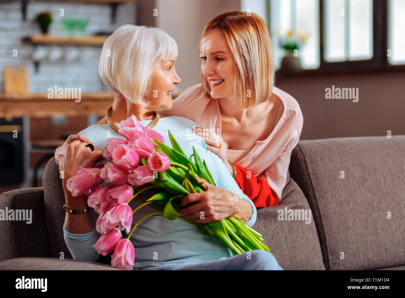 Attractive daughter tenderly looking at elderly d smiling mother - Stock Image