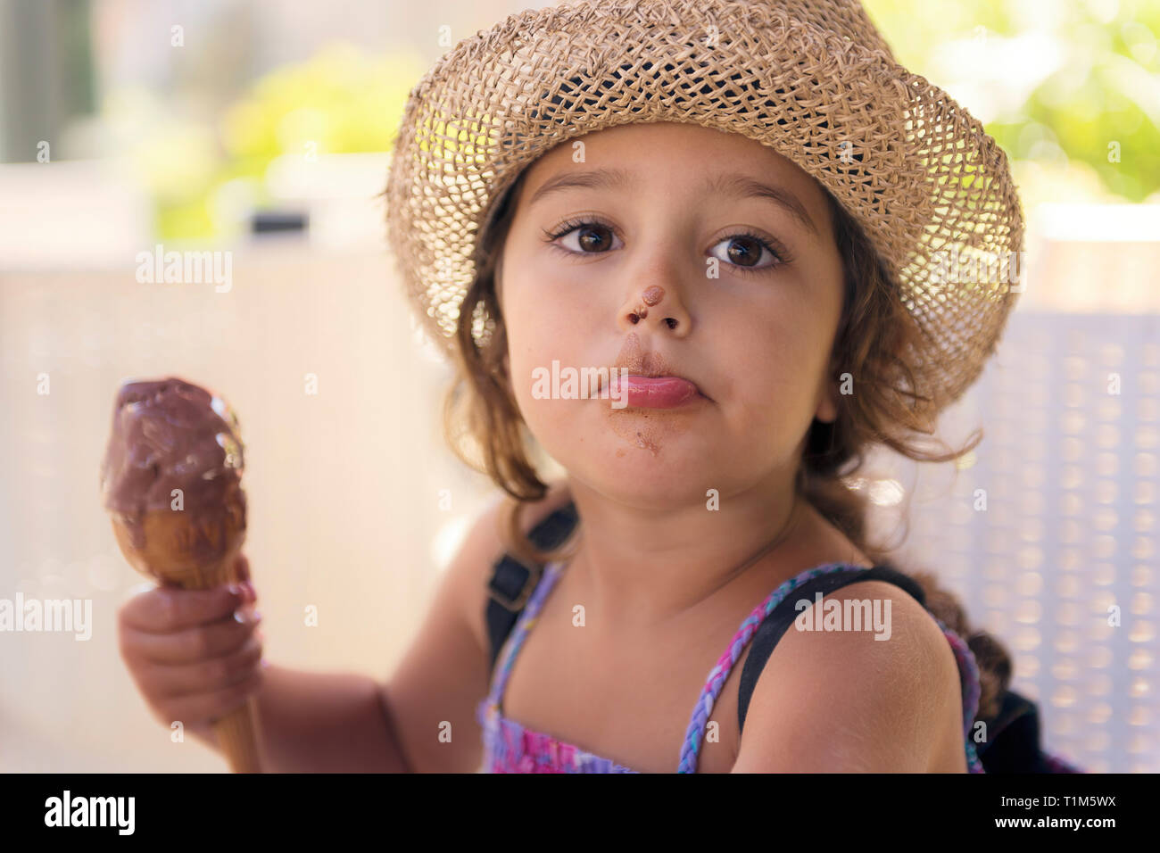 Little girl with straw hat and a sundress enjoys the summer heat eating a refreshing cone of chocolate ice cream, it melts on her hand and she has the Stock Photo