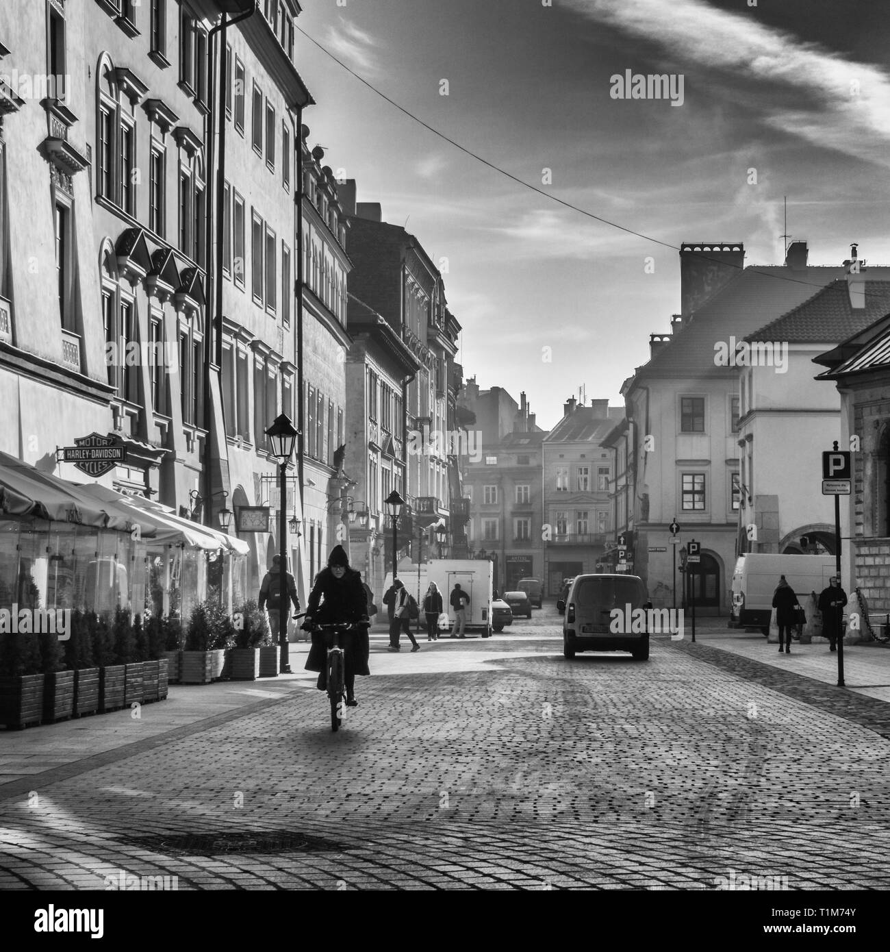 Local woman riding a bicycle down plac maryacki early in the morning with dramatic sun's rays, Krakow Poland - Stock Image