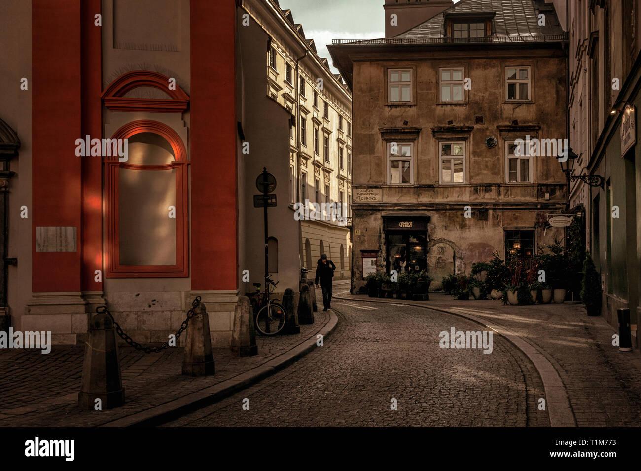 Man walking down Zautek Niewiernego Tomasza with Camelot cafe in the background, Krakow, Poland - Stock Image