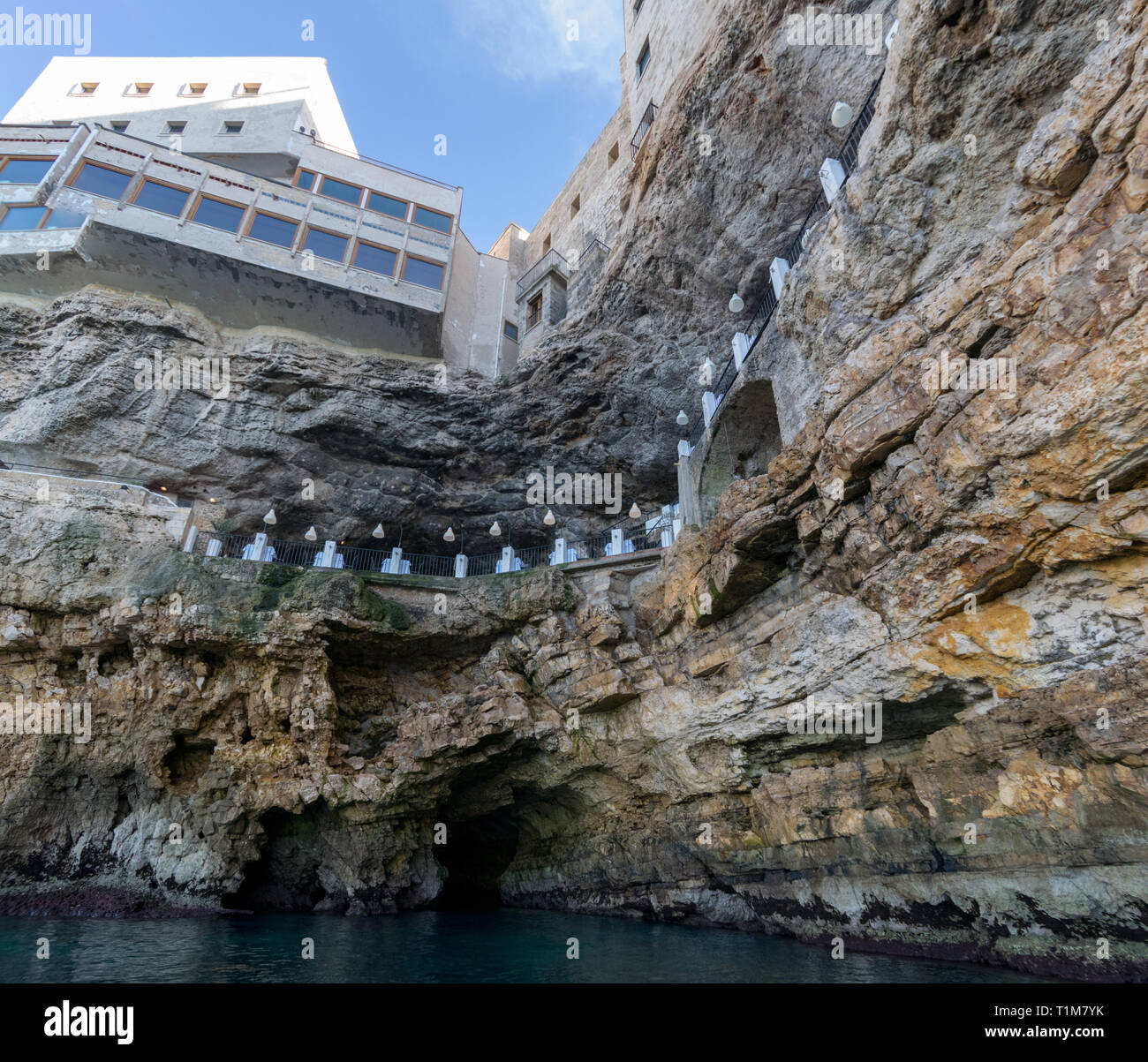 POLIGNANO, ITALY - 16 AUg 2016: The seafront entrance of Grotta Palazzese, a natural sea cave now part of a high end restaurant, in Polignano a Mare,  - Stock Image