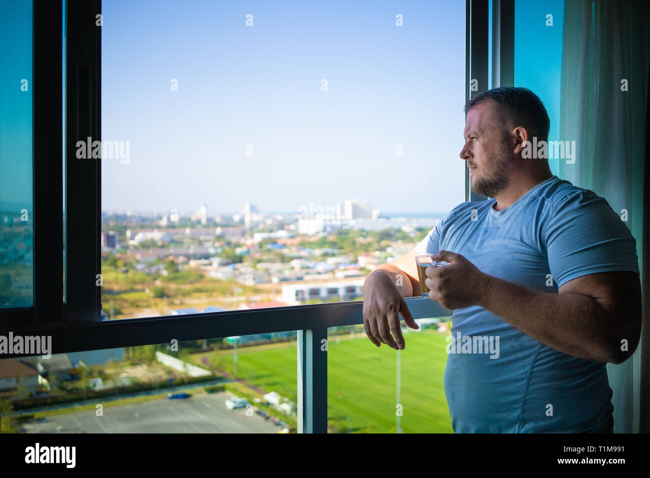 male drinks coffee and looks through  panoramic window smiles in the morning Stock Photo