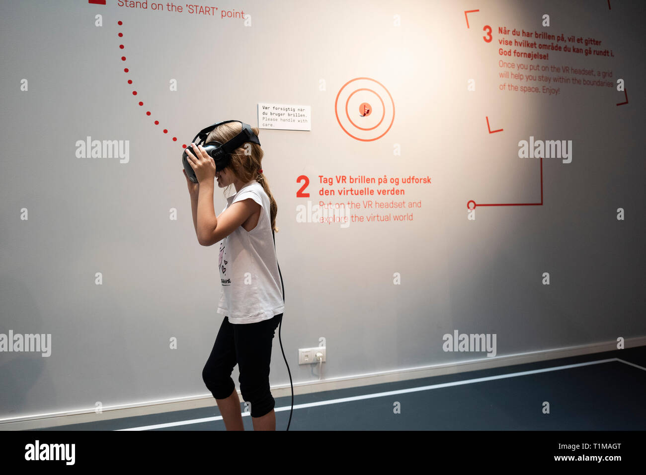 Copenhagen. Denmark. Child using a VR (virtual reality) headset to interact with an exhibit at the Danish Architecture Centre DAC, Bryghuspladsen 10. - Stock Image