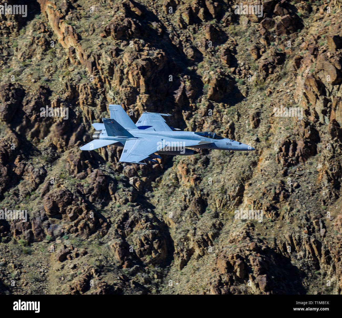 In this shot a Boeing F/A-18C Super Hornet makes a run through Rainbow/Star Wars Canyon in Death Valley National Park, California, USA. - Stock Image