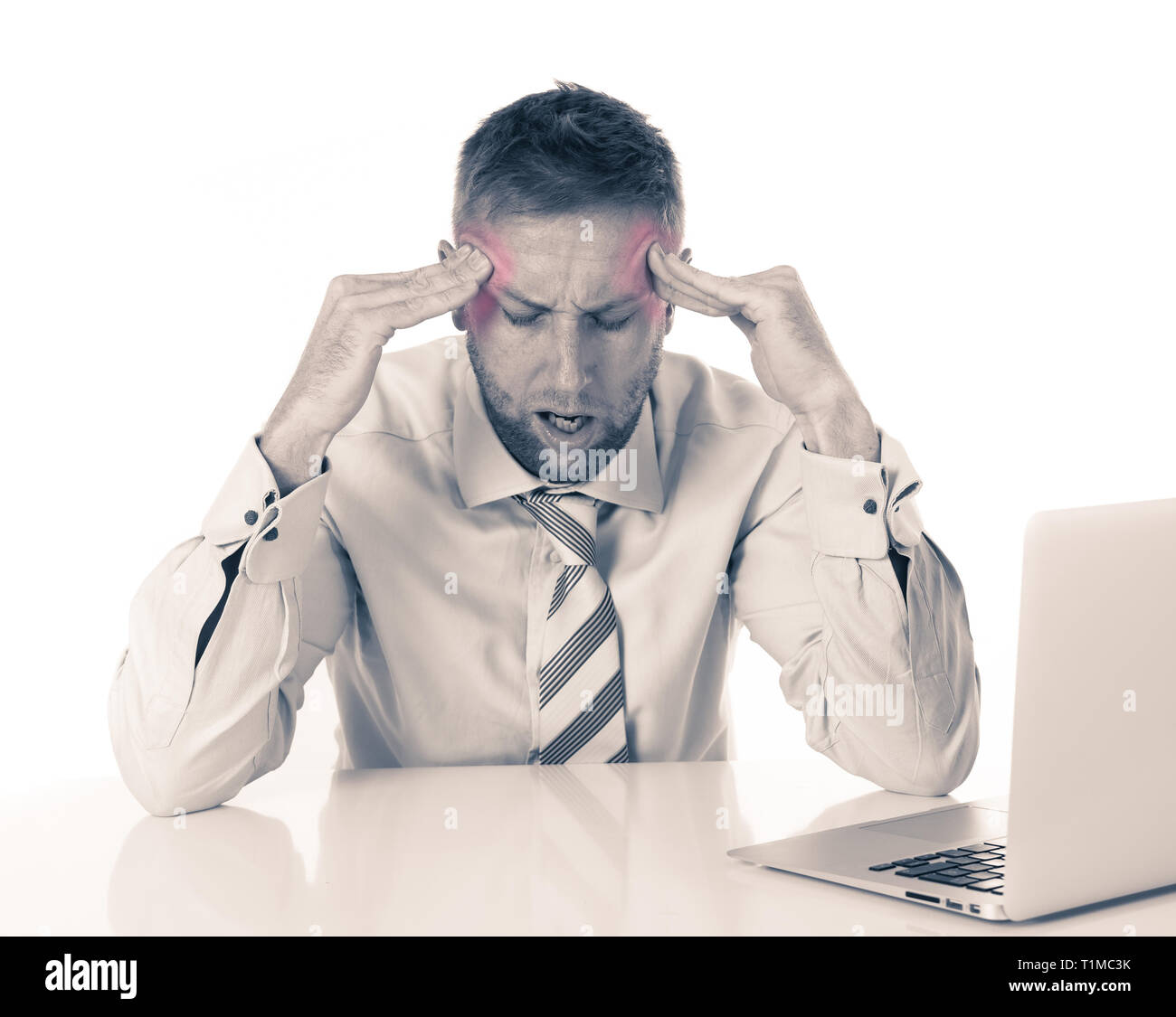 Young handsome tired business man in pain with headache suffering from migraines working on laptop feeling sad sick and overwhelmed. In Stress, Busine - Stock Image