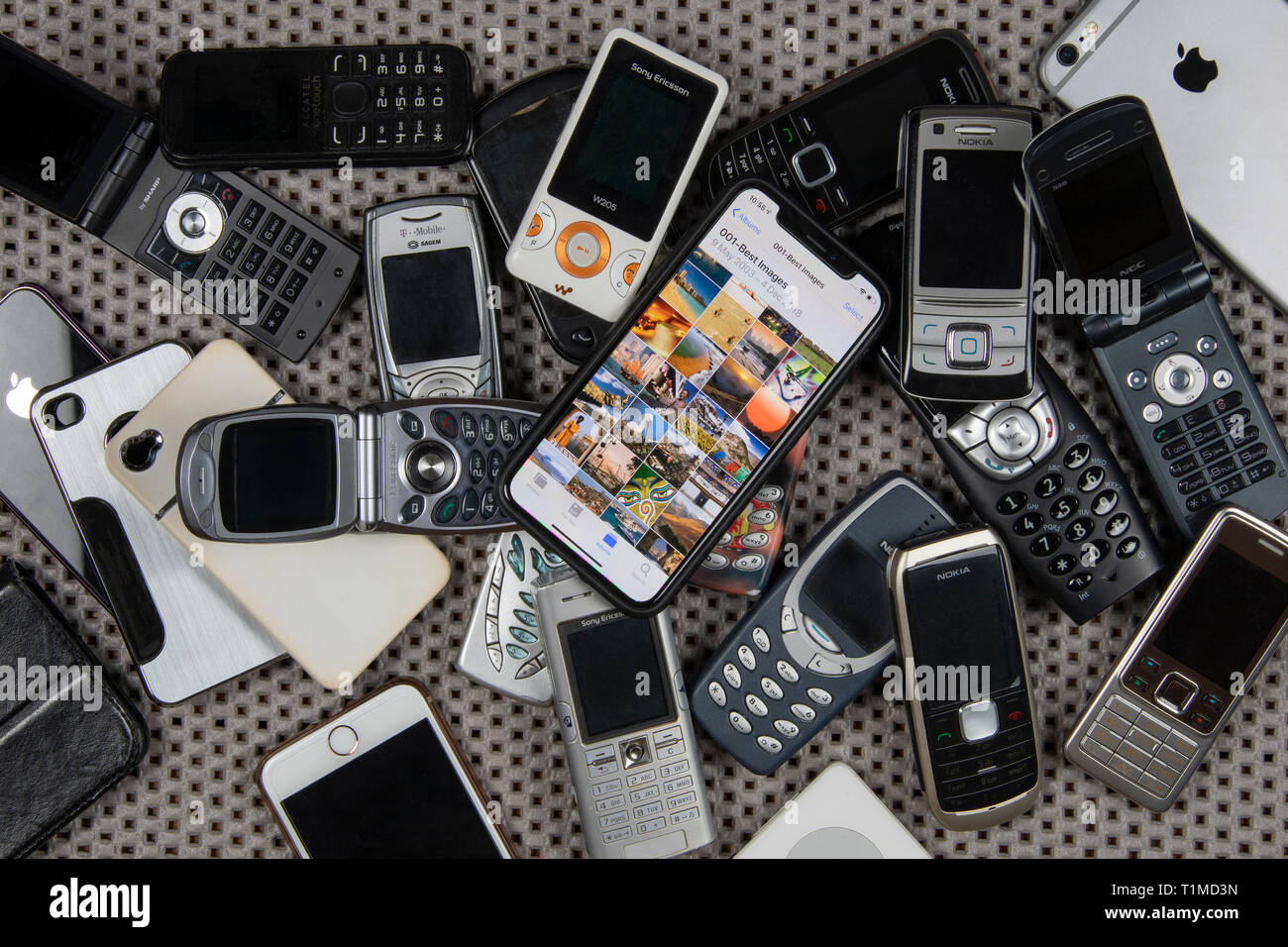 A modern smartphone on a pile of old, obsolete mobile phones. Stock Photo