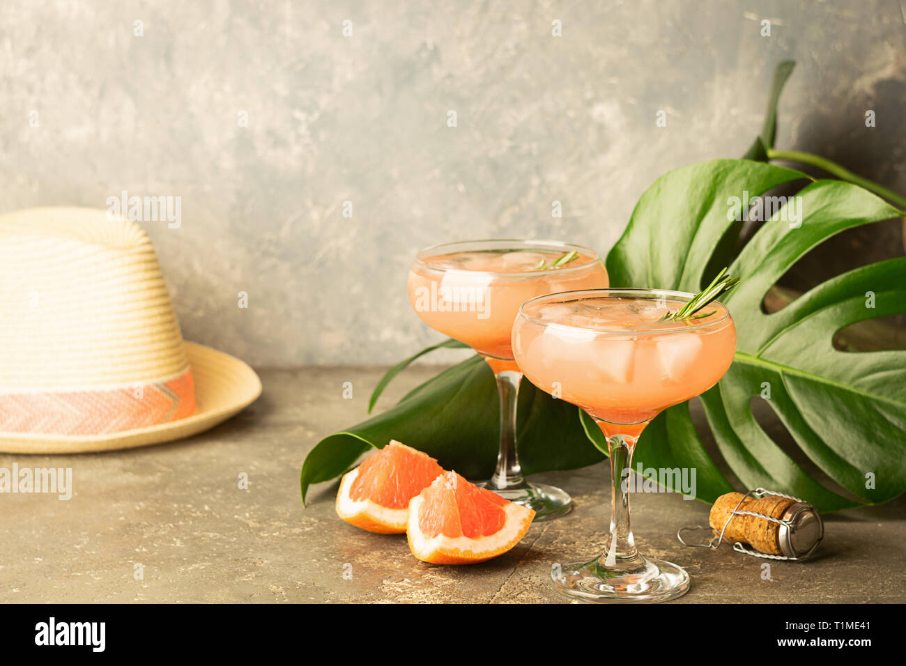 Refreshing grapefruit champagne juice in two glass goblets a concrete background with monster leaves and a summer hat. - Stock Image