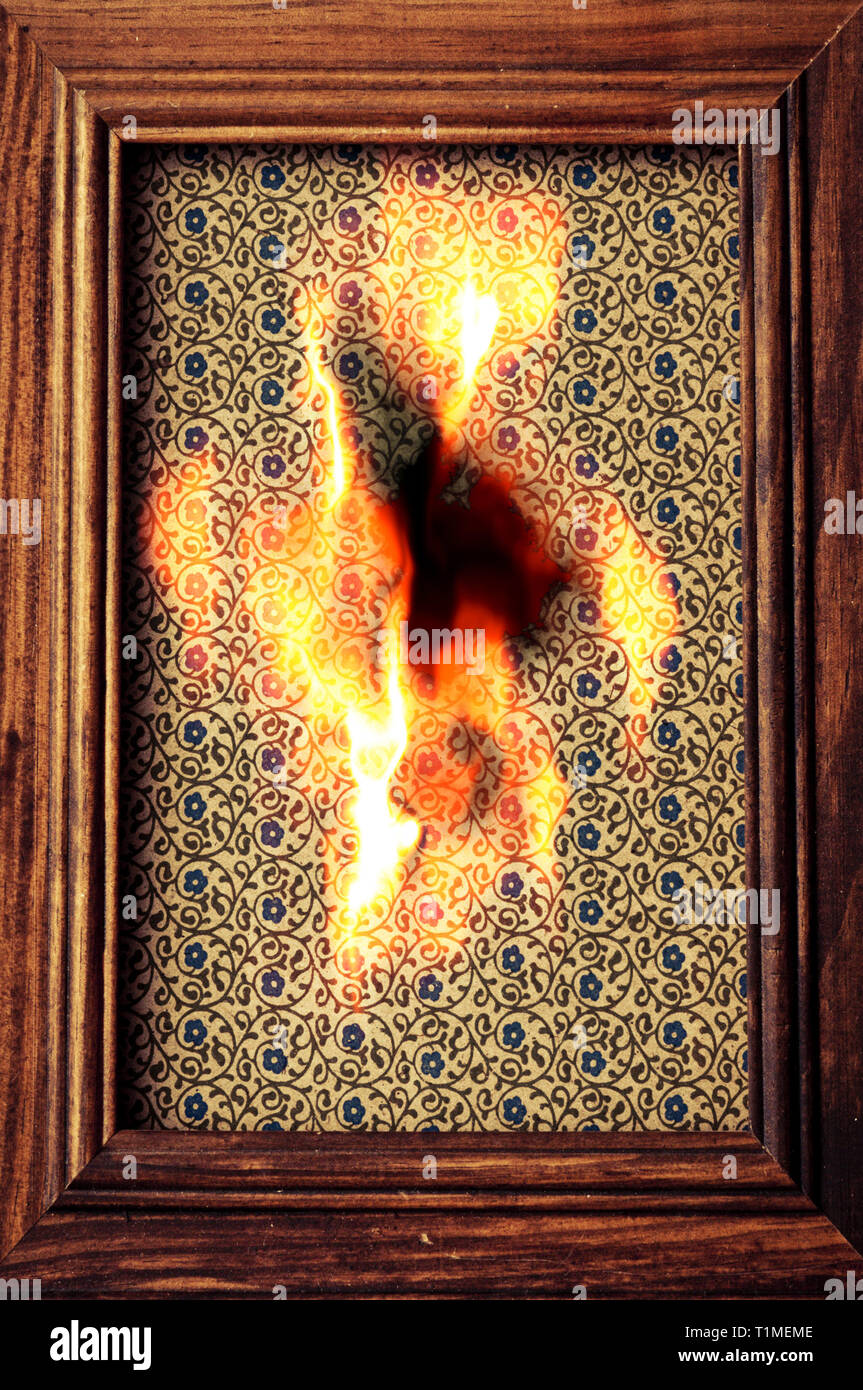 wooden picture frame with a burning wallpaper inside it - Stock Image