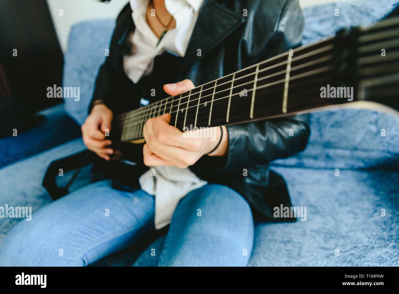 Detail of the fingers of a guitarist placed on the fret of the mast of the guitar playing a chord doing Tapping. - Stock Image