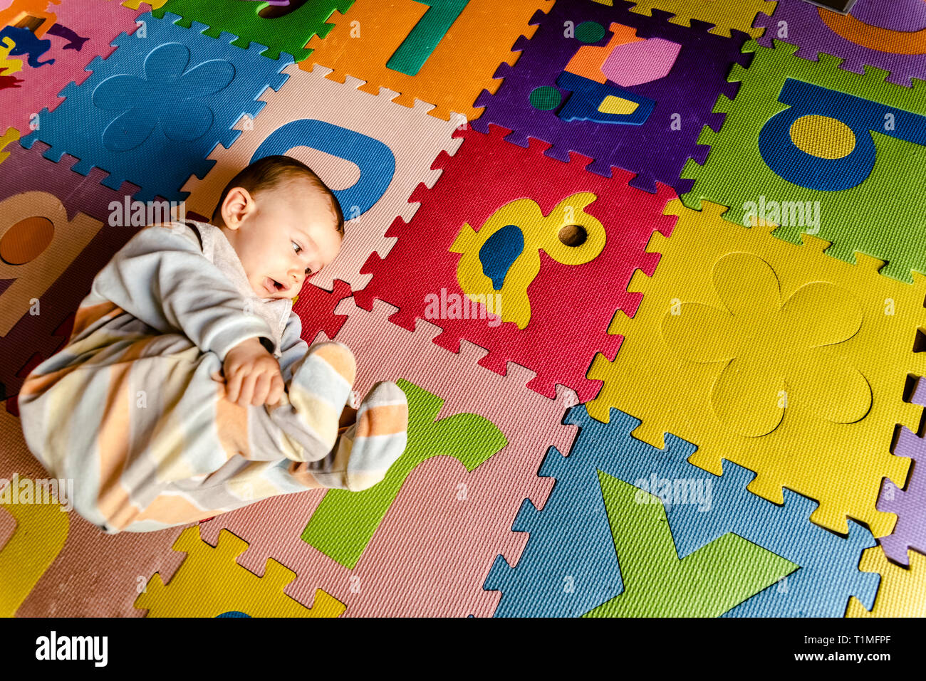 Baby in pajamas doing yoga lying on the floor to develop. - Stock Image