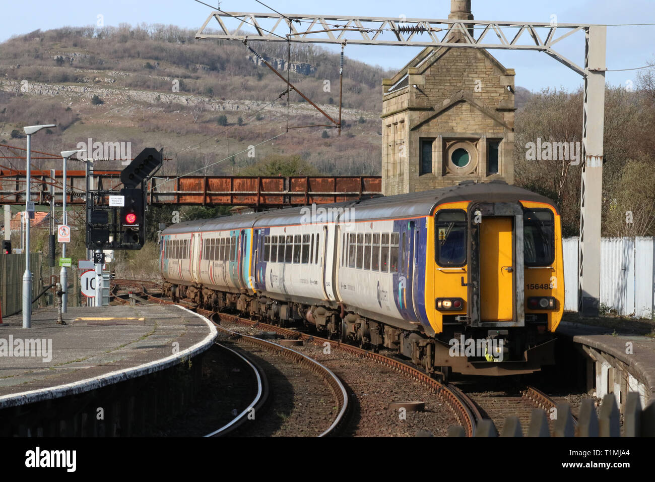 Two class 156 super sprinter diesel multiple unit trains entering Carnforth station, platform 1, with a Northern passenger service on 25th March 2019. - Stock Image