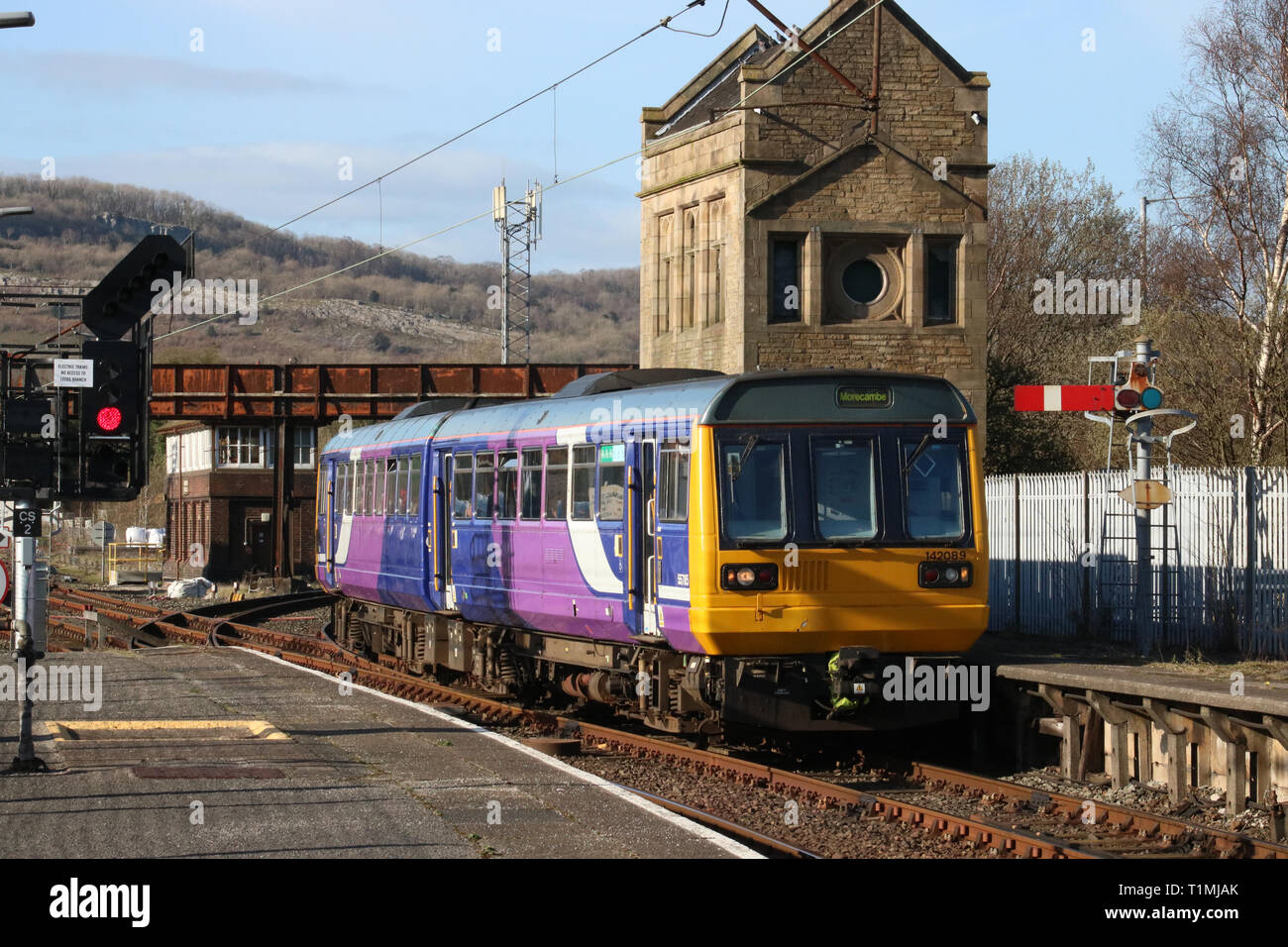 Class 142 Pacer two car diesel multiple unit in Northern livery arriving at Carnforth station with a Leeds to Morecambe train on 25th March 2019. - Stock Image
