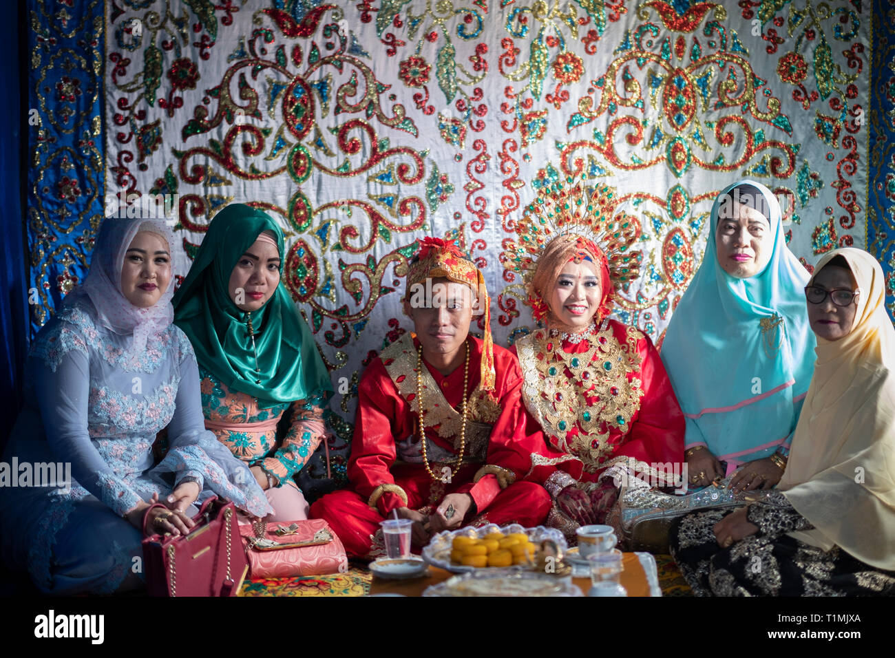 A newly married couple and their family at a wedding celebration, Sulawesi, Indonesia - Stock Image