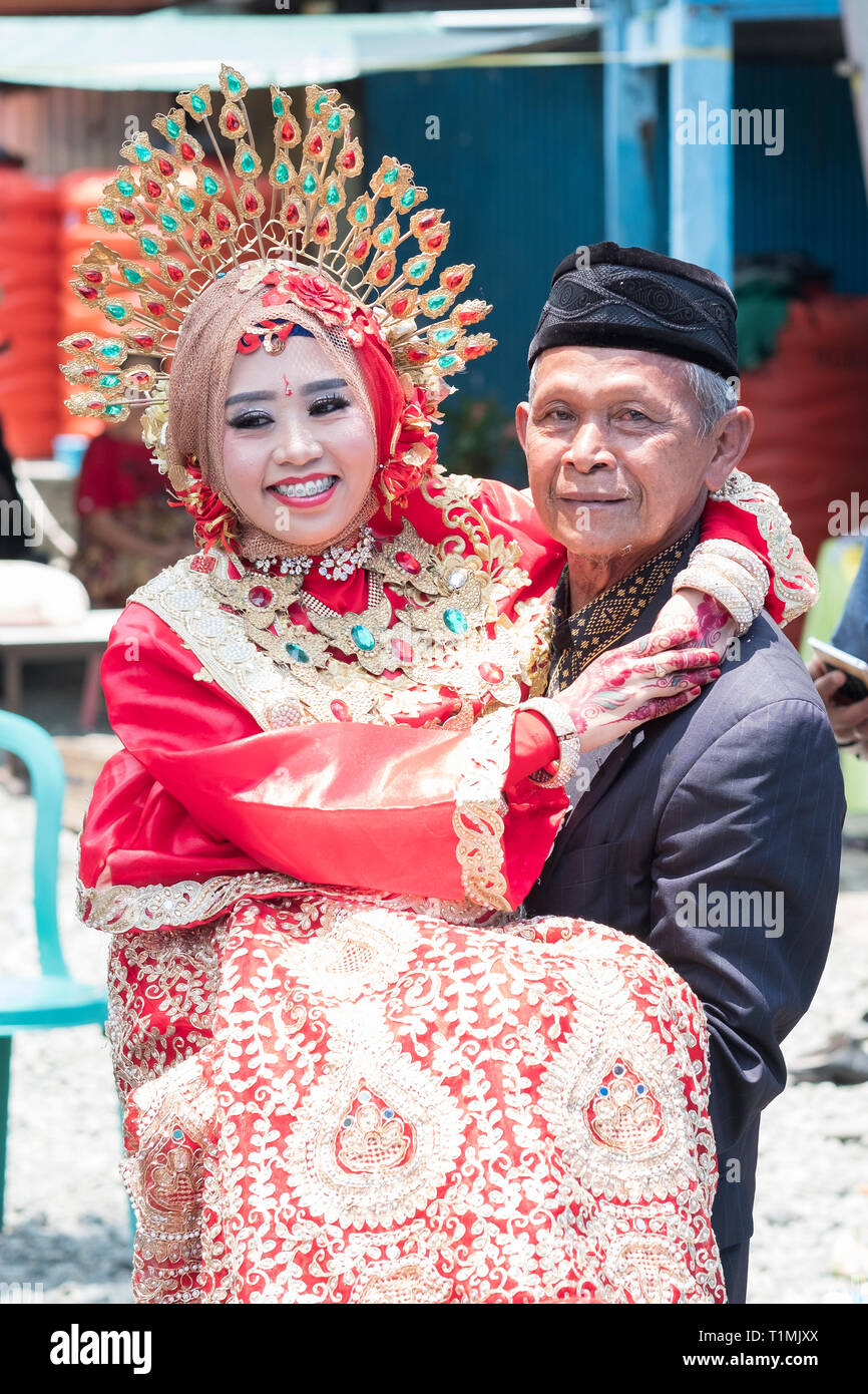 A father and his newly married daughter wearing a traditional Sulawesi wedding dress, Sulawesi, Indonesia - Stock Image
