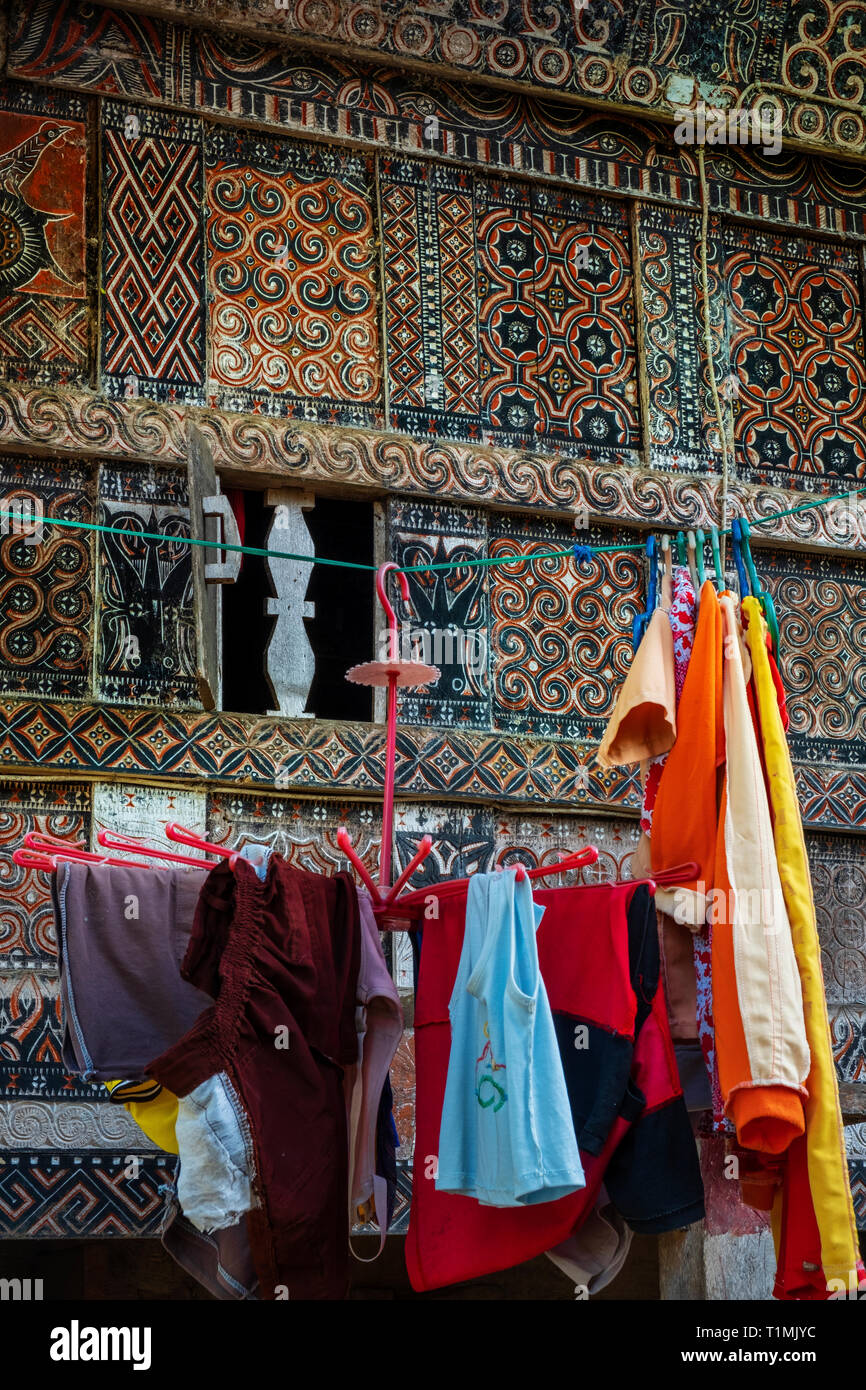 Facade of a Tongokan house in Toraja with laundry drying in the side - Stock Image