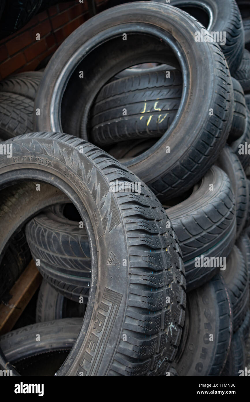 Random pile of used car tyres piled up for resale in a