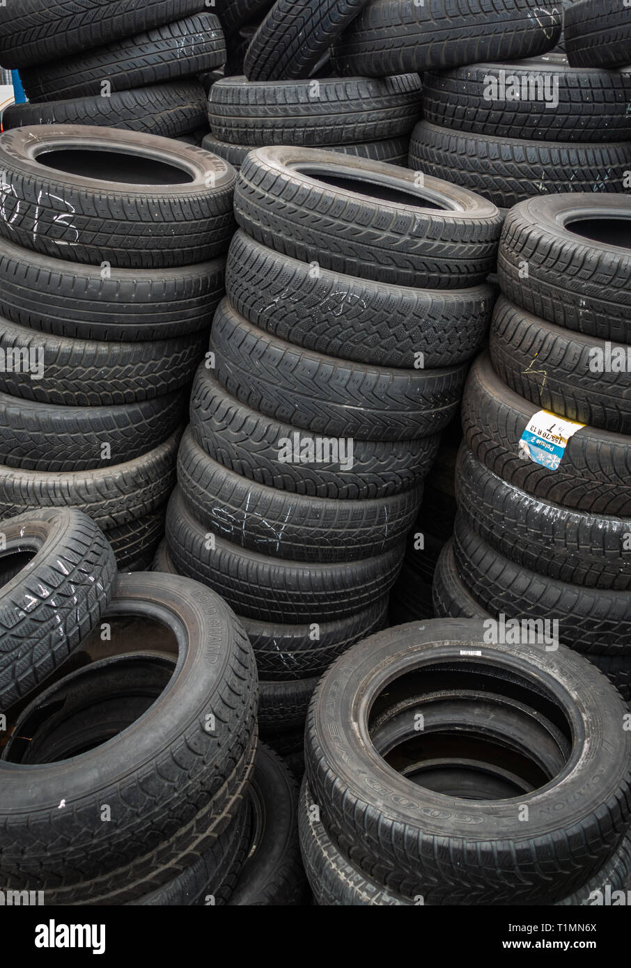 Rows of neatly stacked sed car tyres ready for resale in a distribution centre - Stock Image