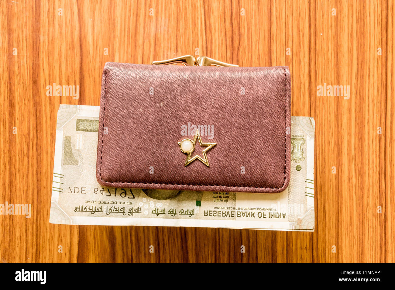 Indian five hundred (500) rupee cash note in brown color wallet leather purse on a wooden table. Business finance economy concept. High angel view wit - Stock Image