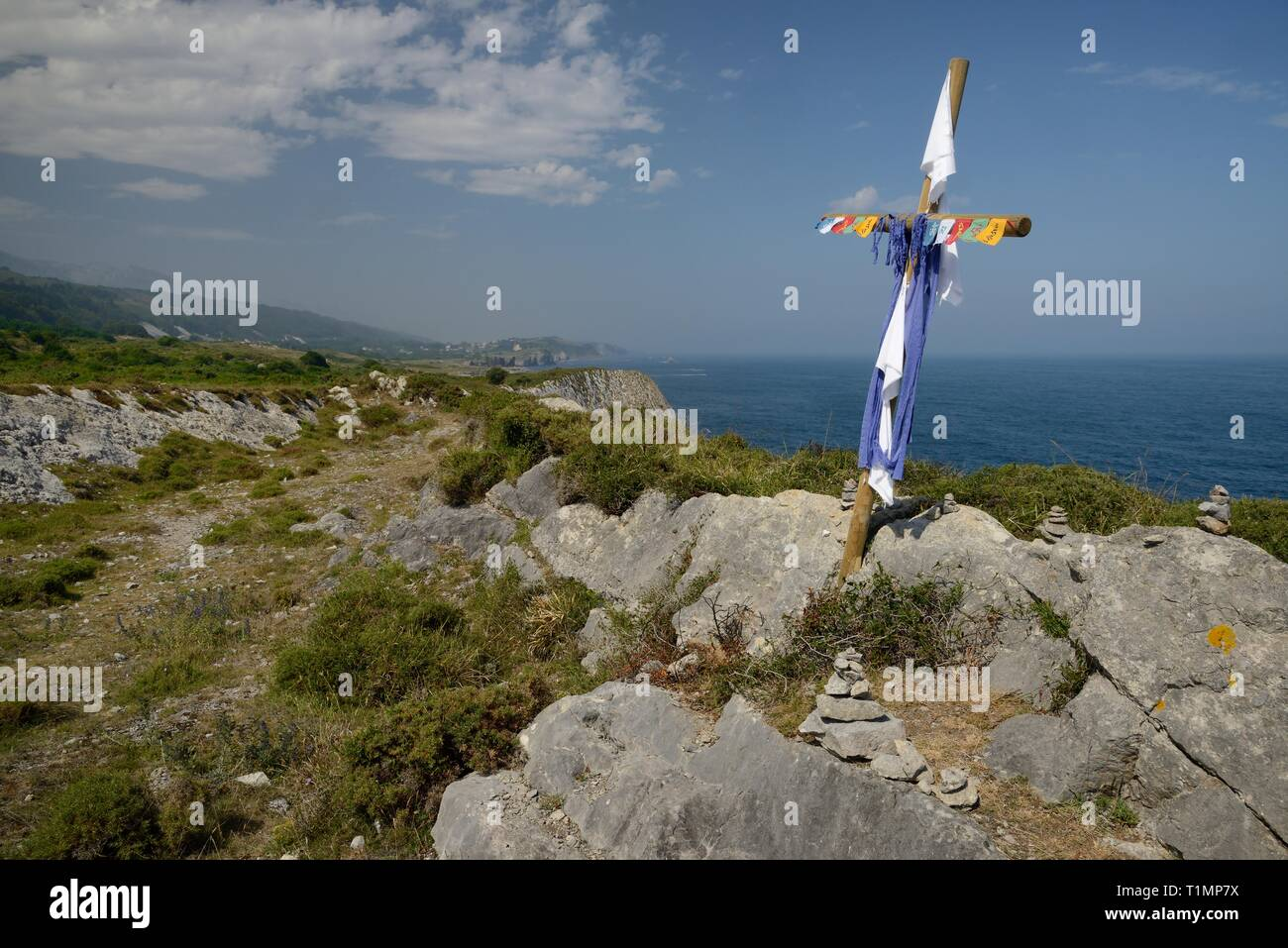 Camino de Santiago coastal route, marked with piles of stones and a cross left by pilgrims, along the cliff edge, near Buelna,  Asturias, Spain. - Stock Image