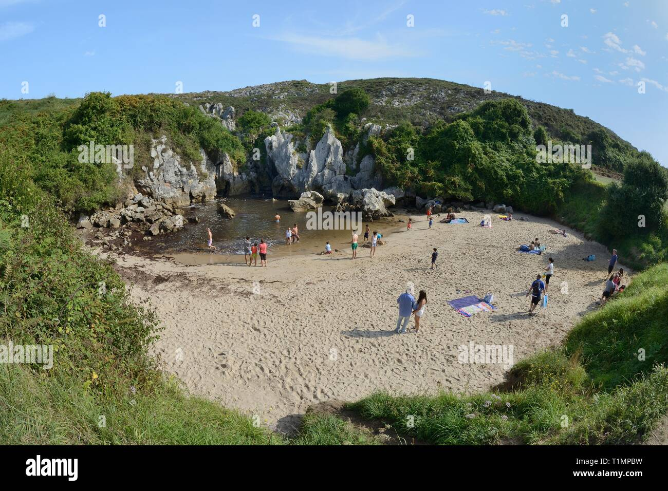 Gulpiyuri beach, an inland beach connected to the coast 100m away by seawater flowing through eroded channels in limestone rock, Naves, Asturias, Spai - Stock Image