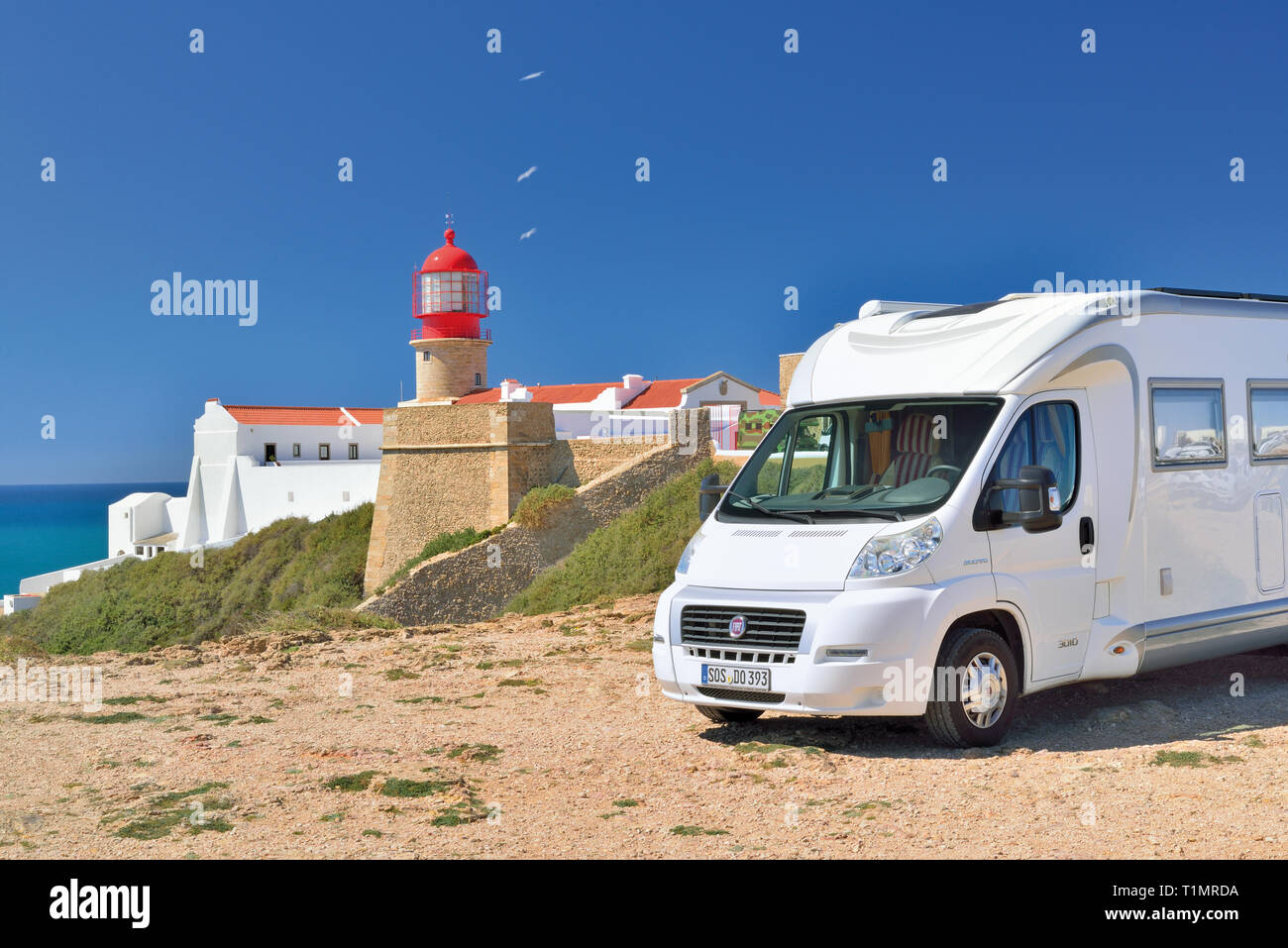 Motor home parking near red lighthouse with white washed building and baby blue sky on a sunny day Stock Photo