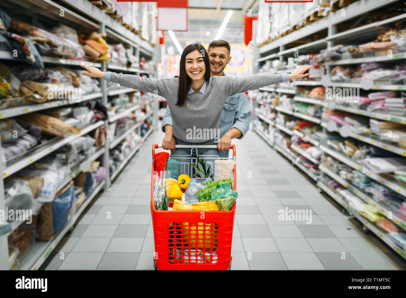 Playful Couple With Cart Full Of Goods In Store Stock Photo