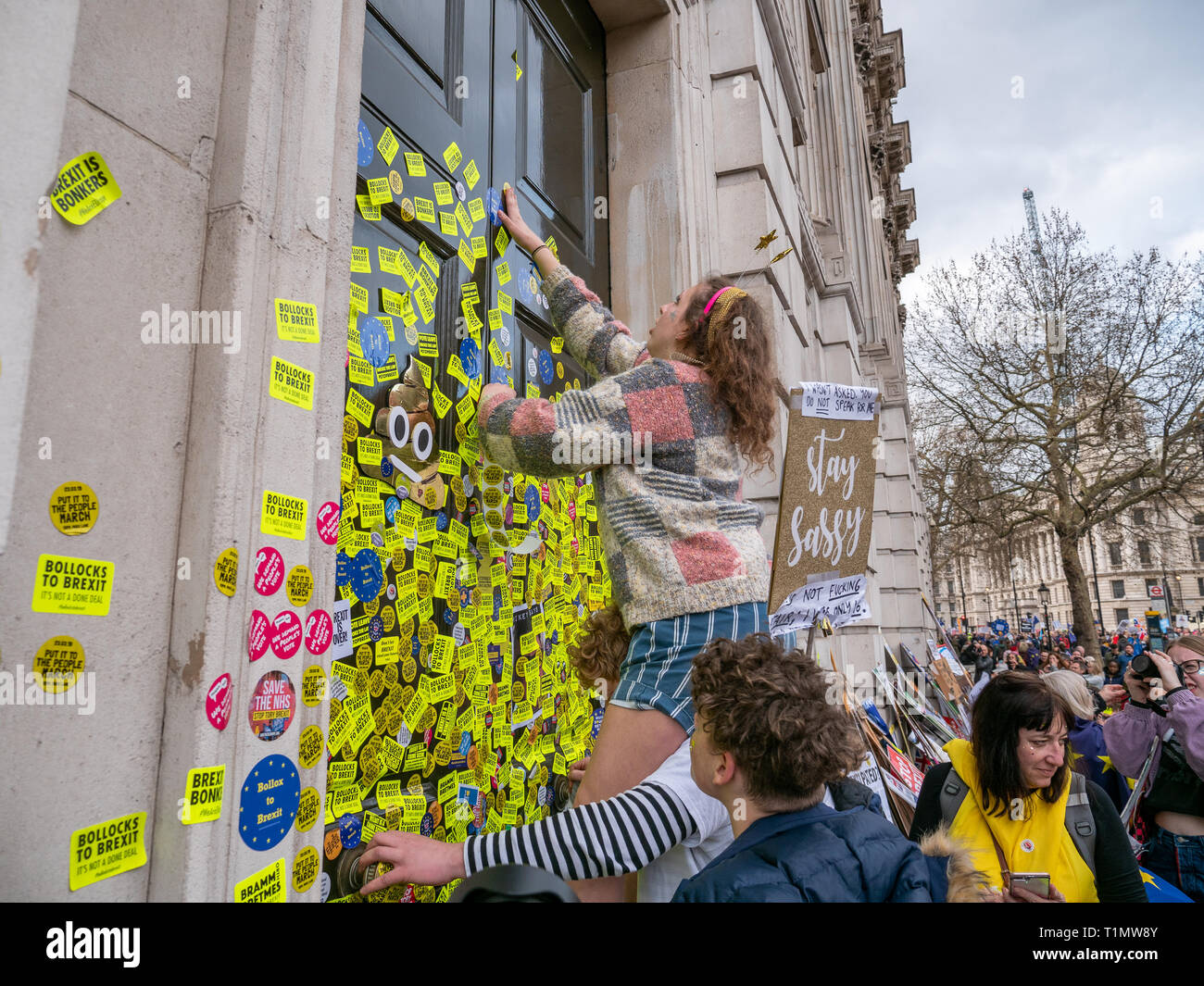 Demonstrators putting anti Brexit stickers on door of Cabinet Office building during the People's Vote march, 23 March 2019, Whitehall, London, UK - Stock Image
