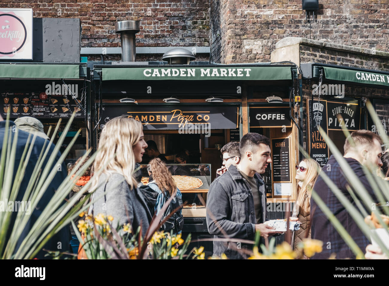 London, UK - March 23,2019: People walking past pizza food stall inside Camden Market, London. Started with 16 stalls in March 1974, Camden Market is  Stock Photo