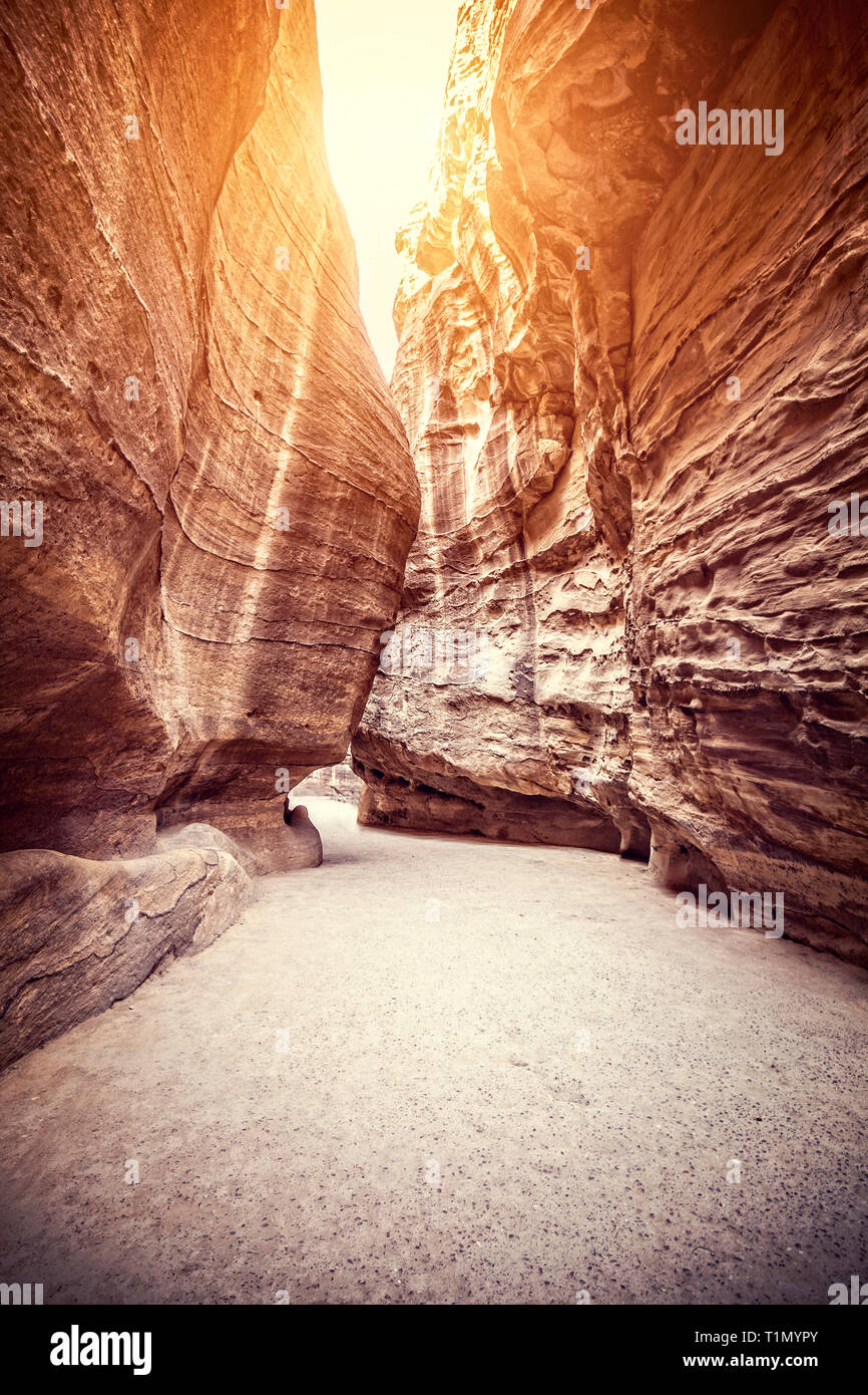 Suggestive route inside the sandstone canyons leading to the treasury of Petra, Jordan. Sunset light. - Stock Image