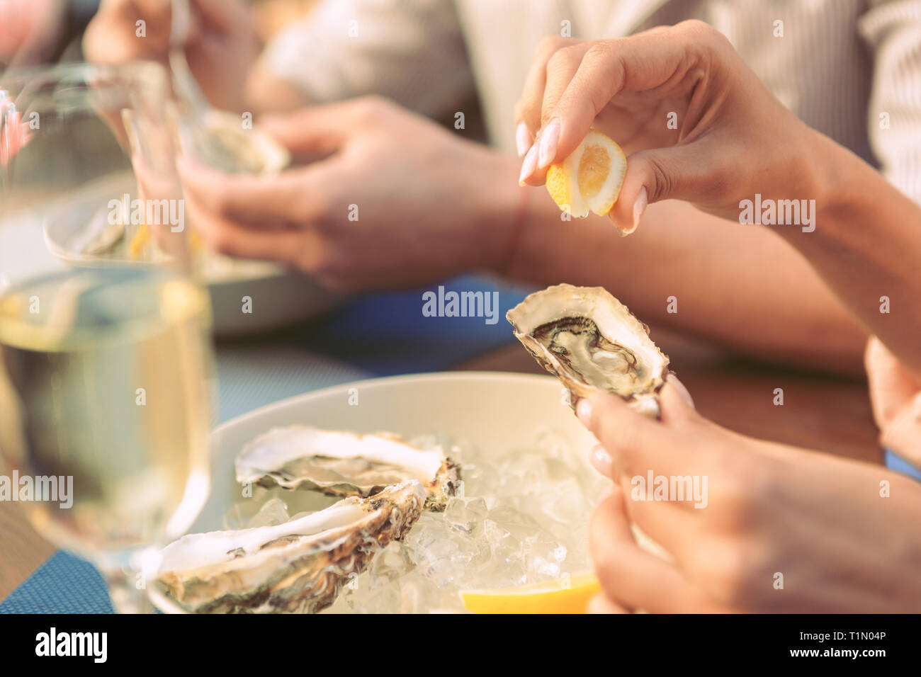 Gentle lady carrying piece of lemon and squeezing it on fresh oyster - Stock Image