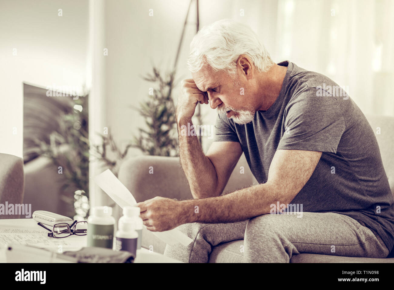 Aging mister clutching his head in despair while holding papers - Stock Image
