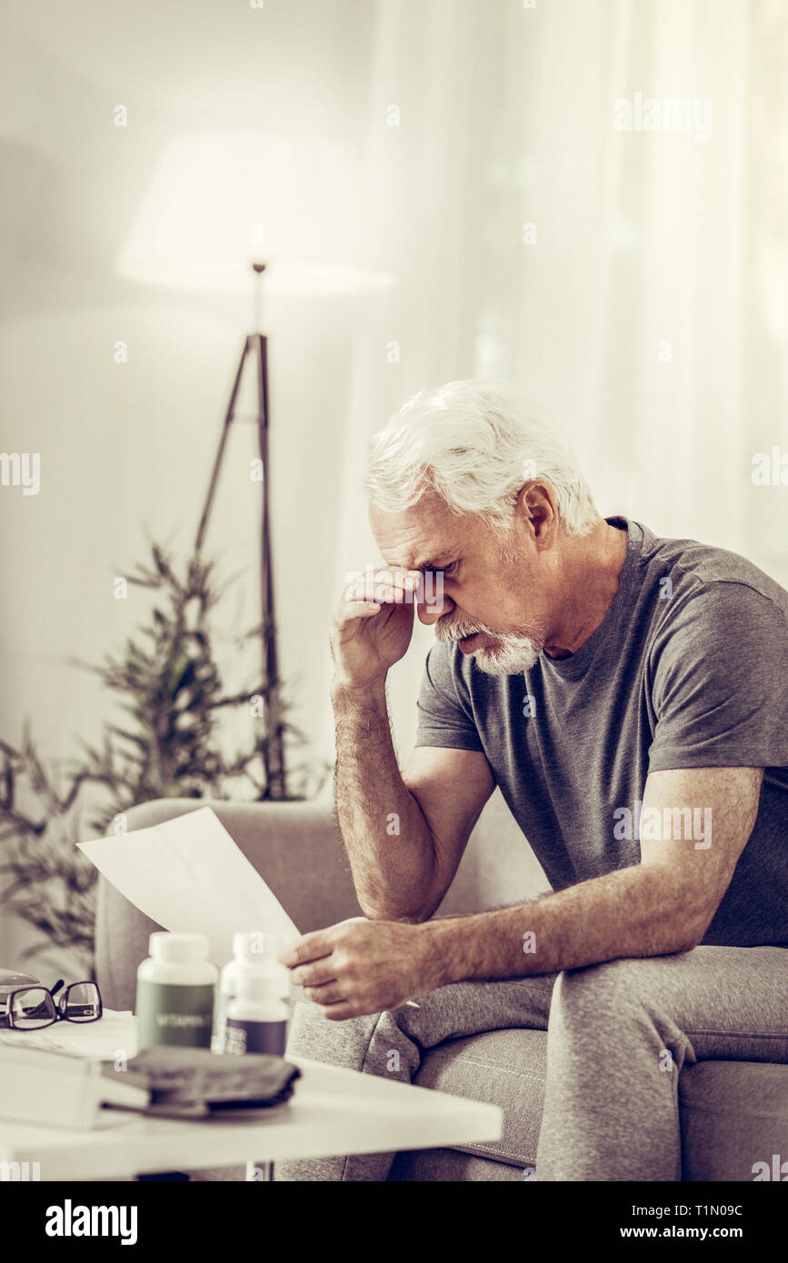 Aged mister sitting on sofa and clutching head in shock - Stock Image